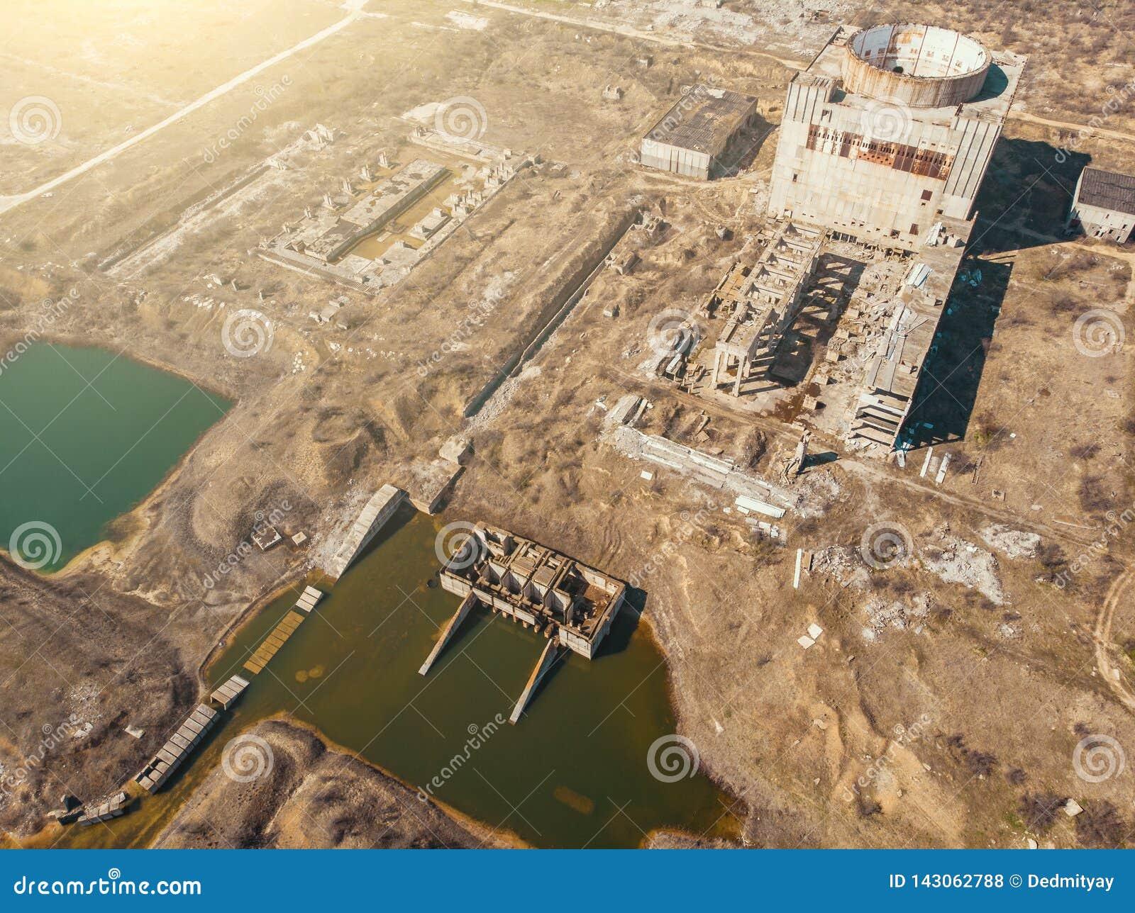 Vista aérea de la central nuclear abandonada y arruinada y de las pequeñas charcas de enfriamiento, atmósfera apocalíptica del po