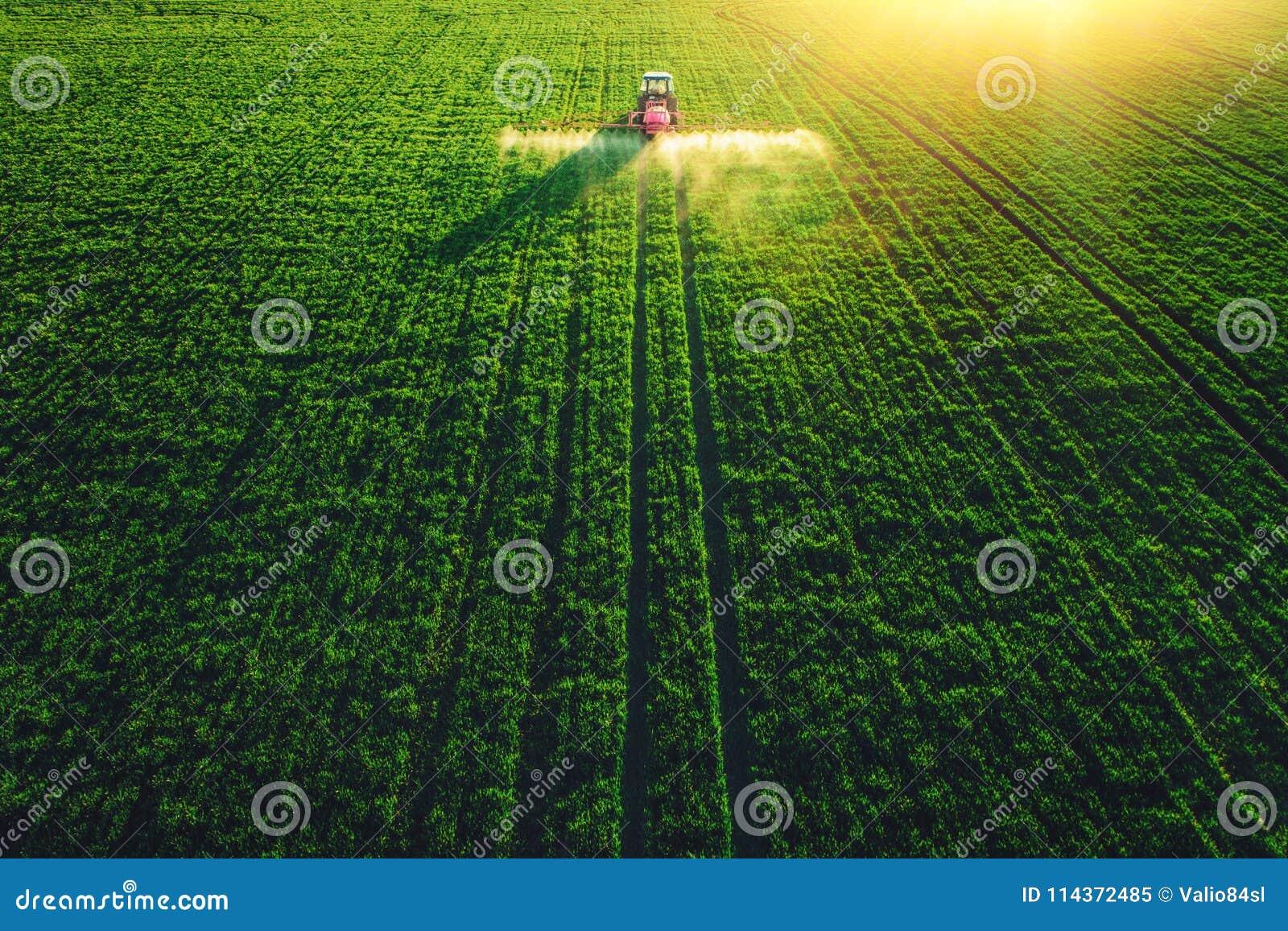 Vista aérea del tractor de cultivo que ara y que rocía en campo