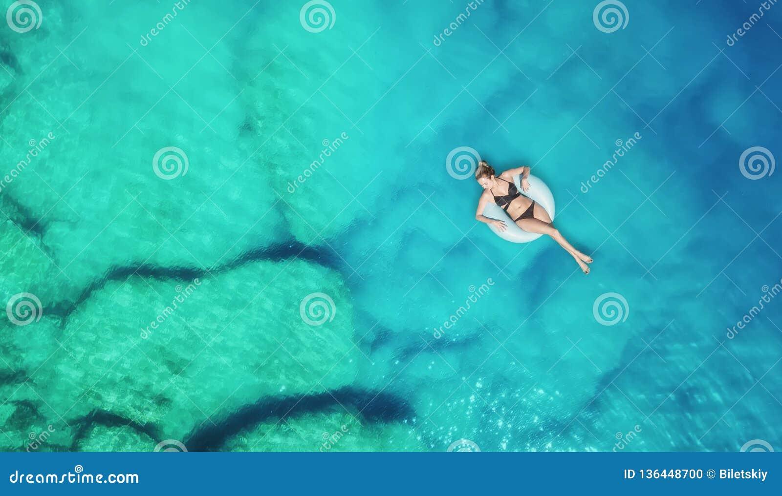 Vista aérea na menina no mar Água de turquesa do ar como um fundo do ar