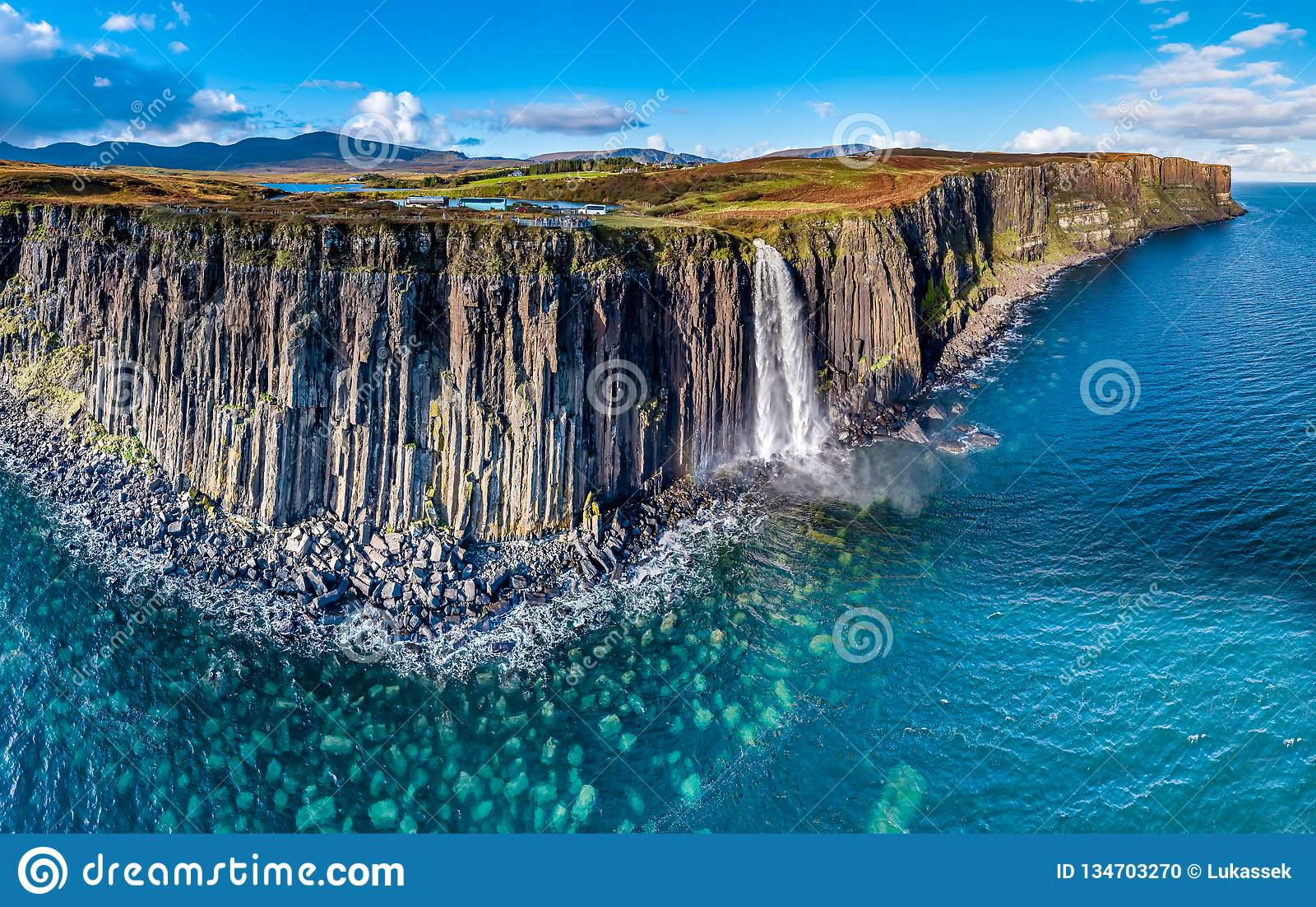 Vista aerea della linea costiera drammatica alle scogliere da Staffin con la cascata famosa della roccia del kilt - isola di Skye