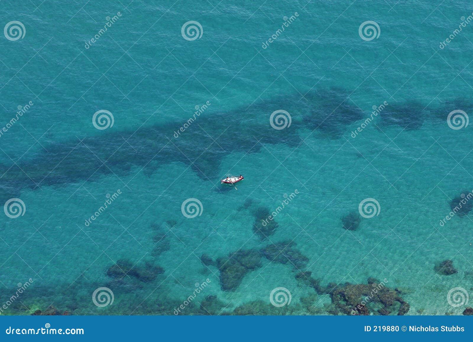 Vista aerea di acqua blu libera e della barca gialla
