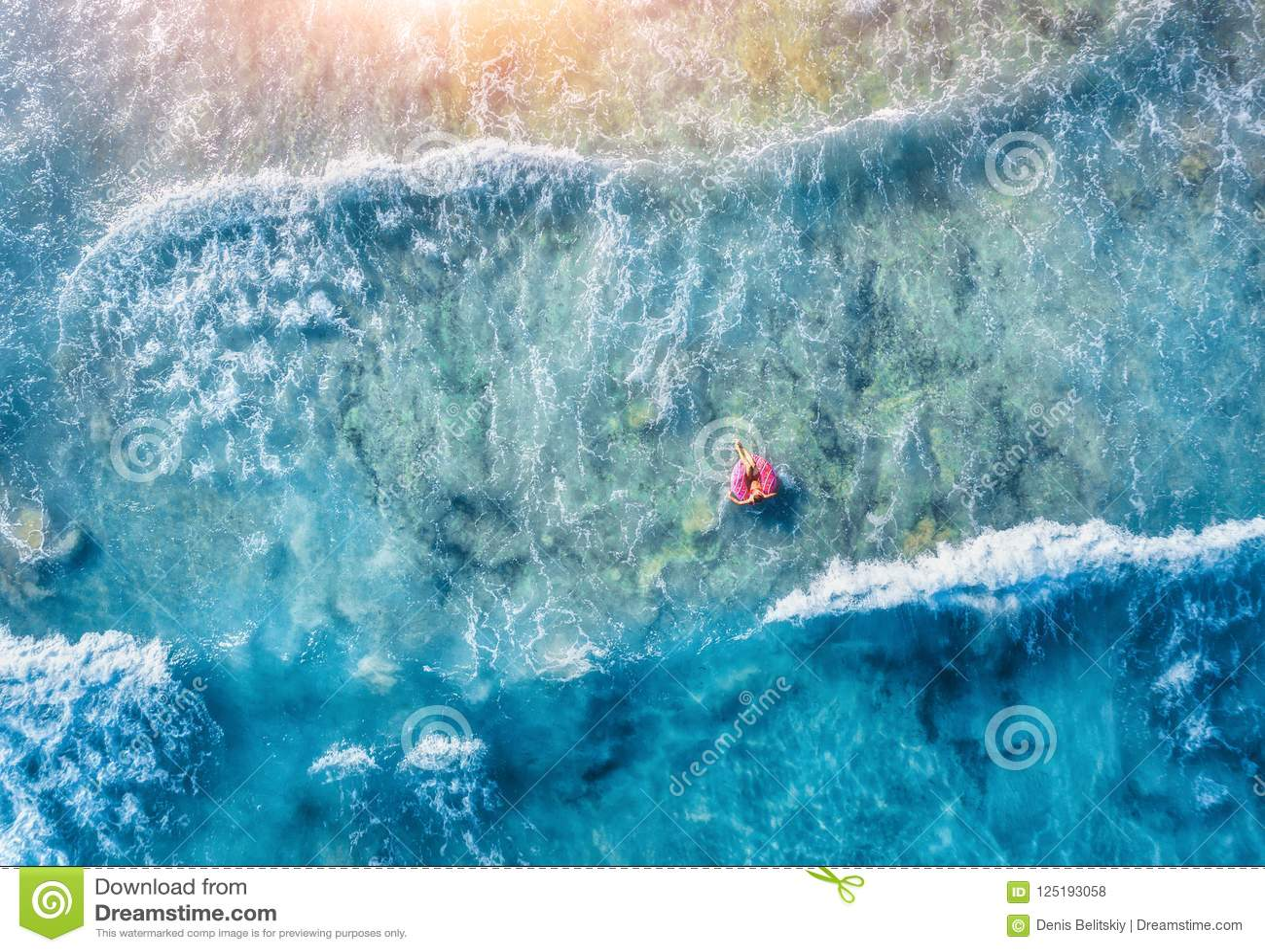 Vista aerea di nuoto esile della giovane donna sull anello di nuotata della ciambella