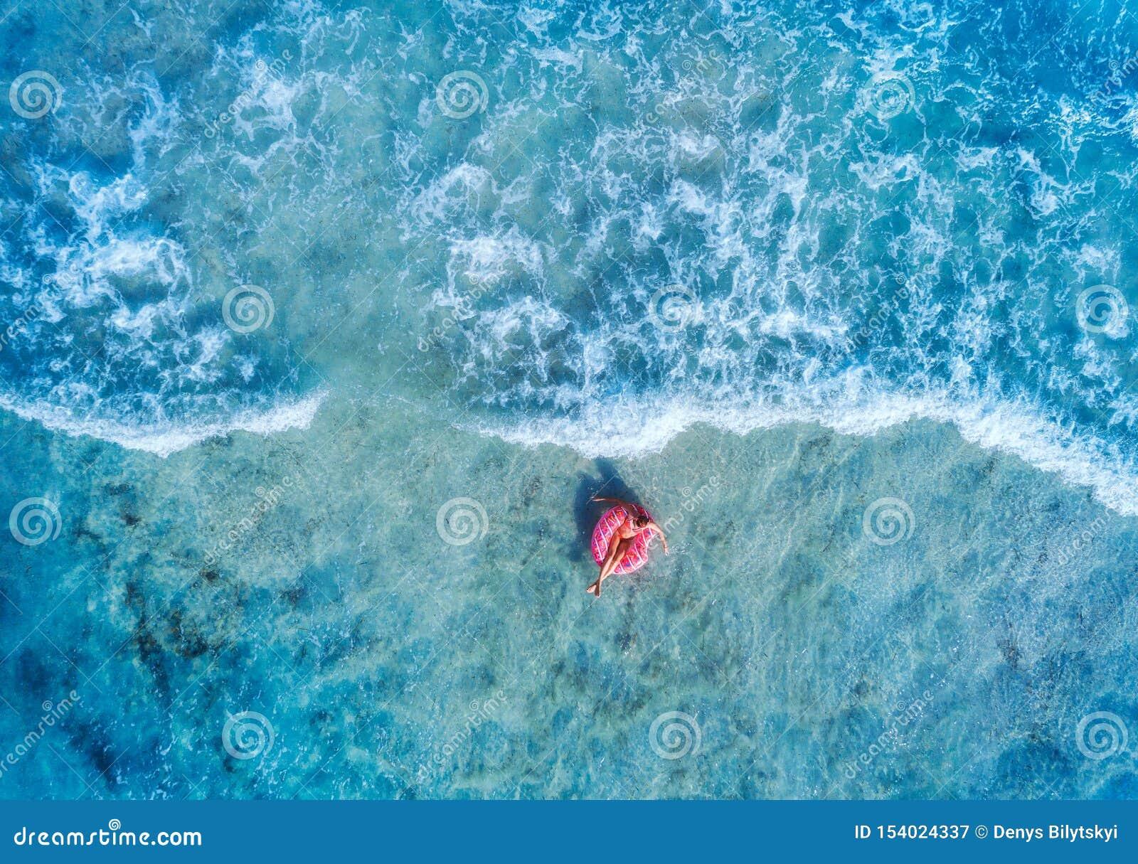Vista aerea di un nuoto della donna con l anello rosa di nuotata della ciambella
