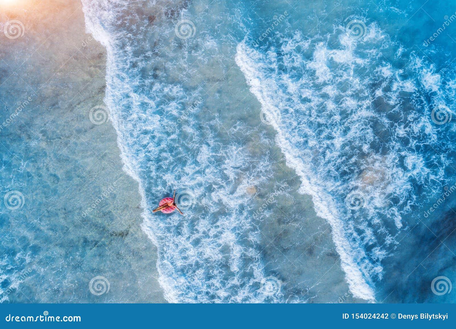 Vista aerea di un nuoto della giovane donna con l anello di nuotata della ciambella