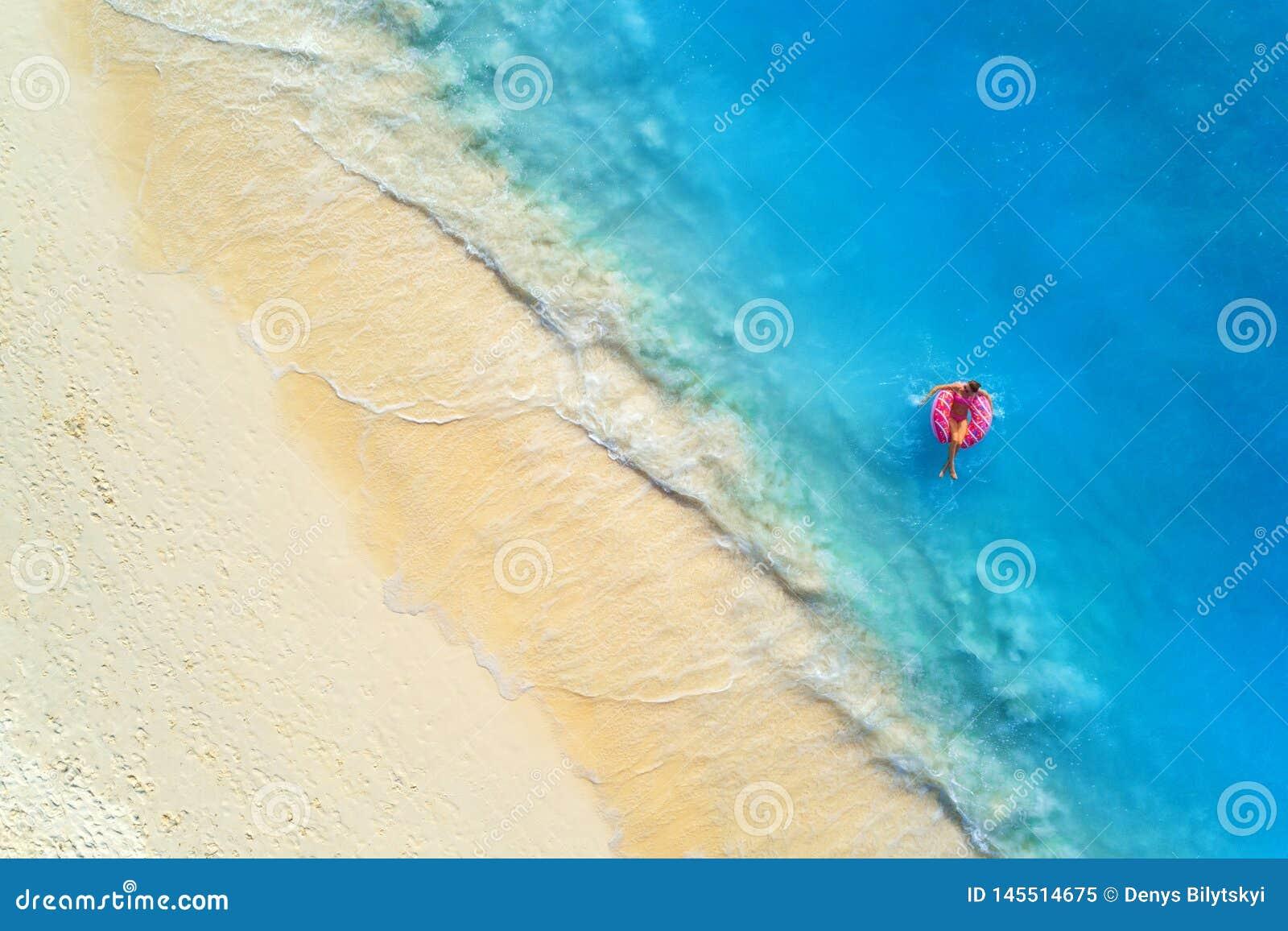 Vista aerea di una donna di nuoto nel mare al tramonto