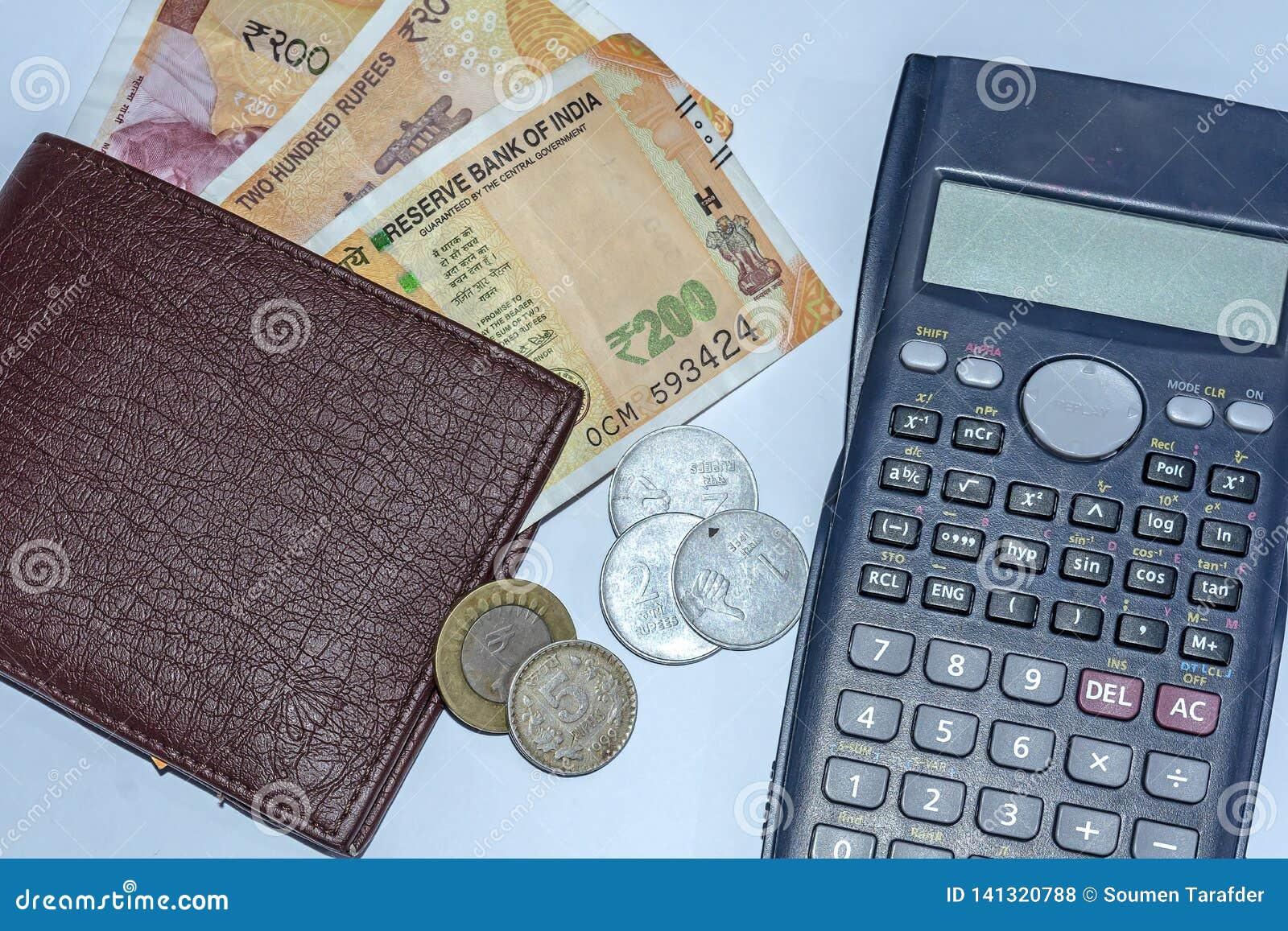 Vista alta vicina del calcolatore, del portafoglio con le 200 rupie indiane nuovissime di banconote e delle monete da 1,2,10 rupi