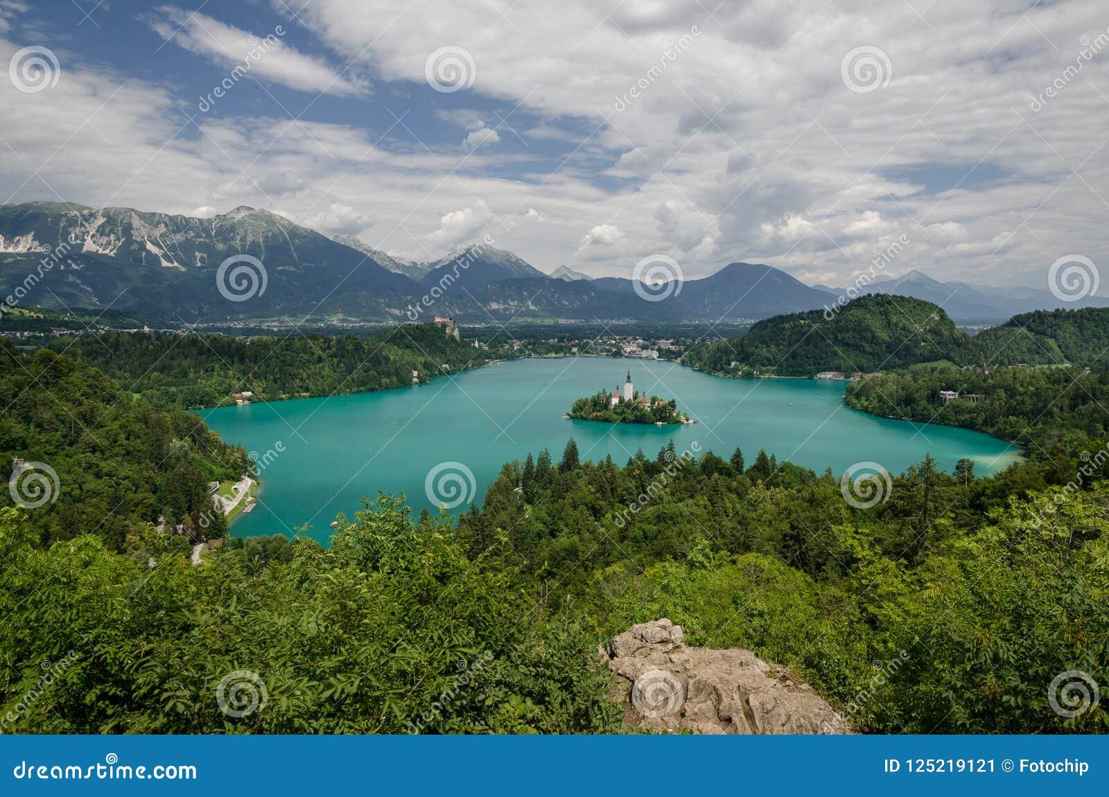 Vista ao lago sangrado com a igreja do St Marys da suposição na ilha pequena Sangrado, Slovenia, Europa