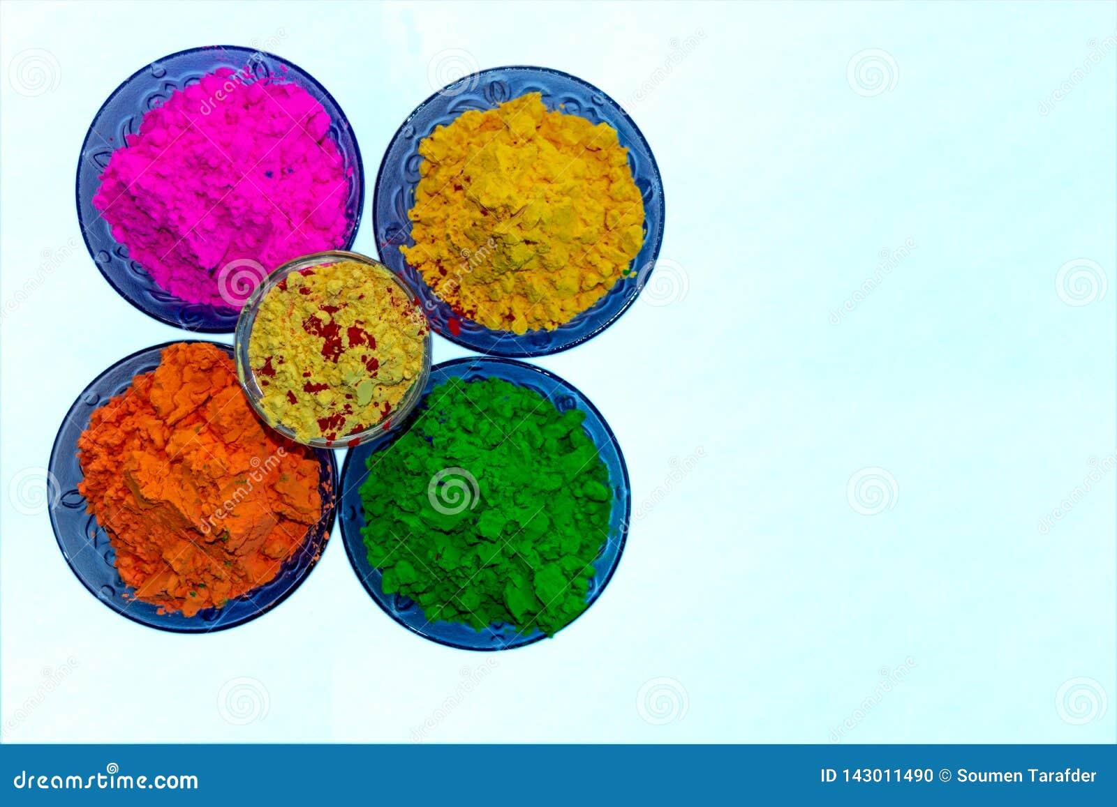Vista ascendente cercana de los polvos orgánicos coloridos de Holi en cuencos azules del color