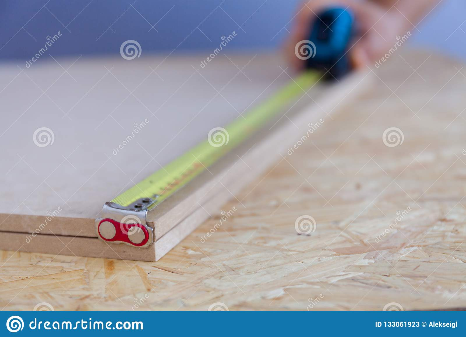 Vista ascendente próxima da madeira de medição da mão de um homem com uma fita handyman medida