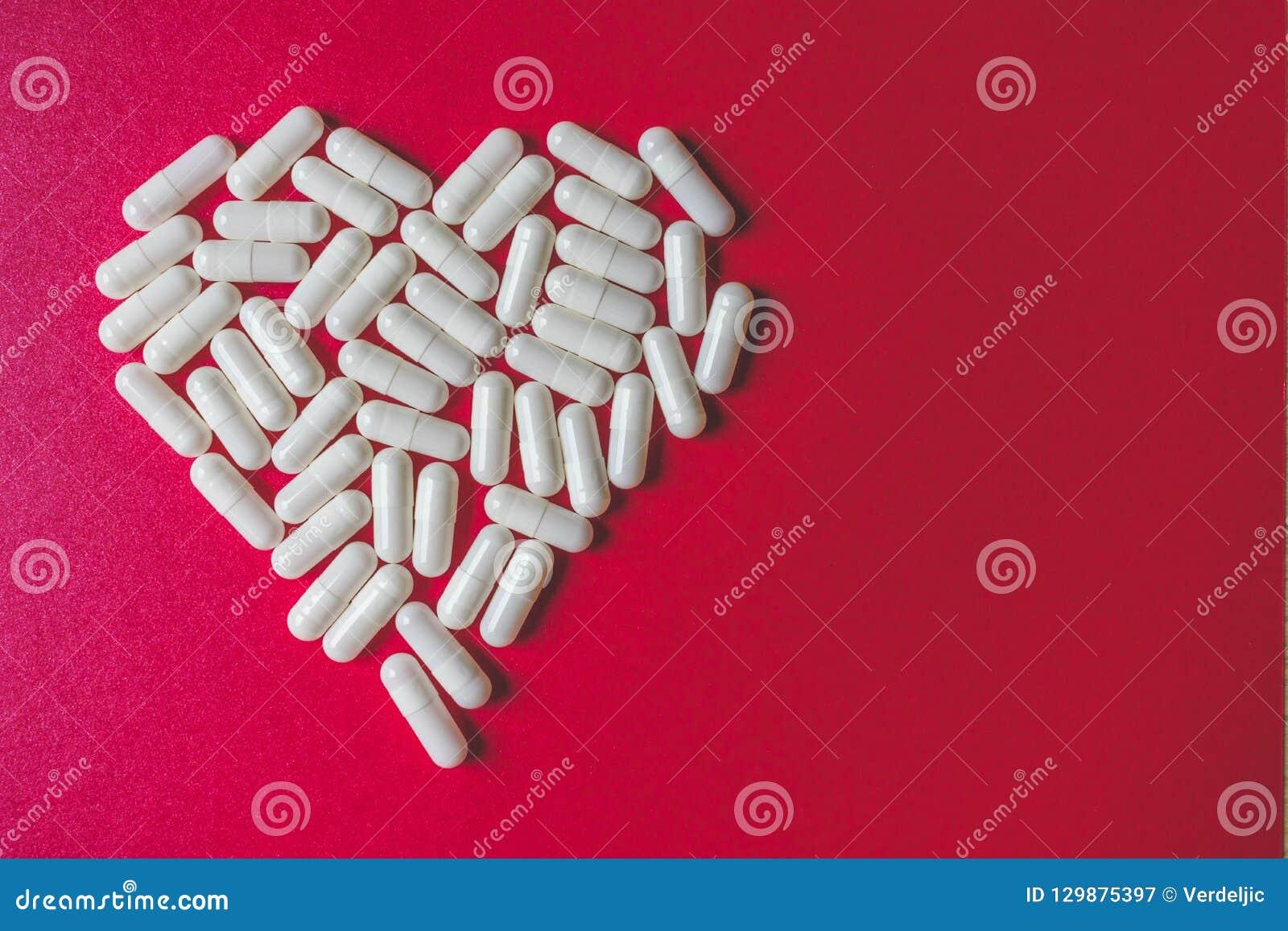Vista ascendente próxima das cápsulas brancas que formam um coração no fundo vermelho com espaço