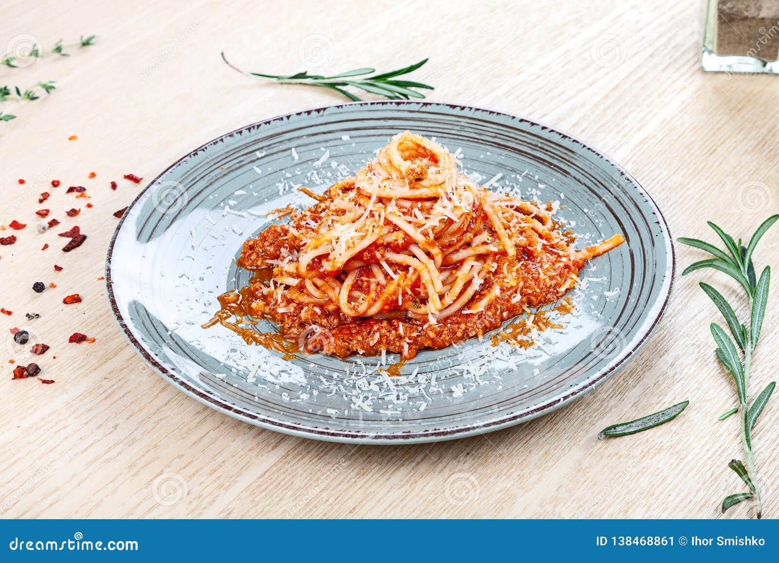 Vista ascendente próxima na massa italiana tradicional com tomate, ervas e especiarias de cereja no fundo de madeira
