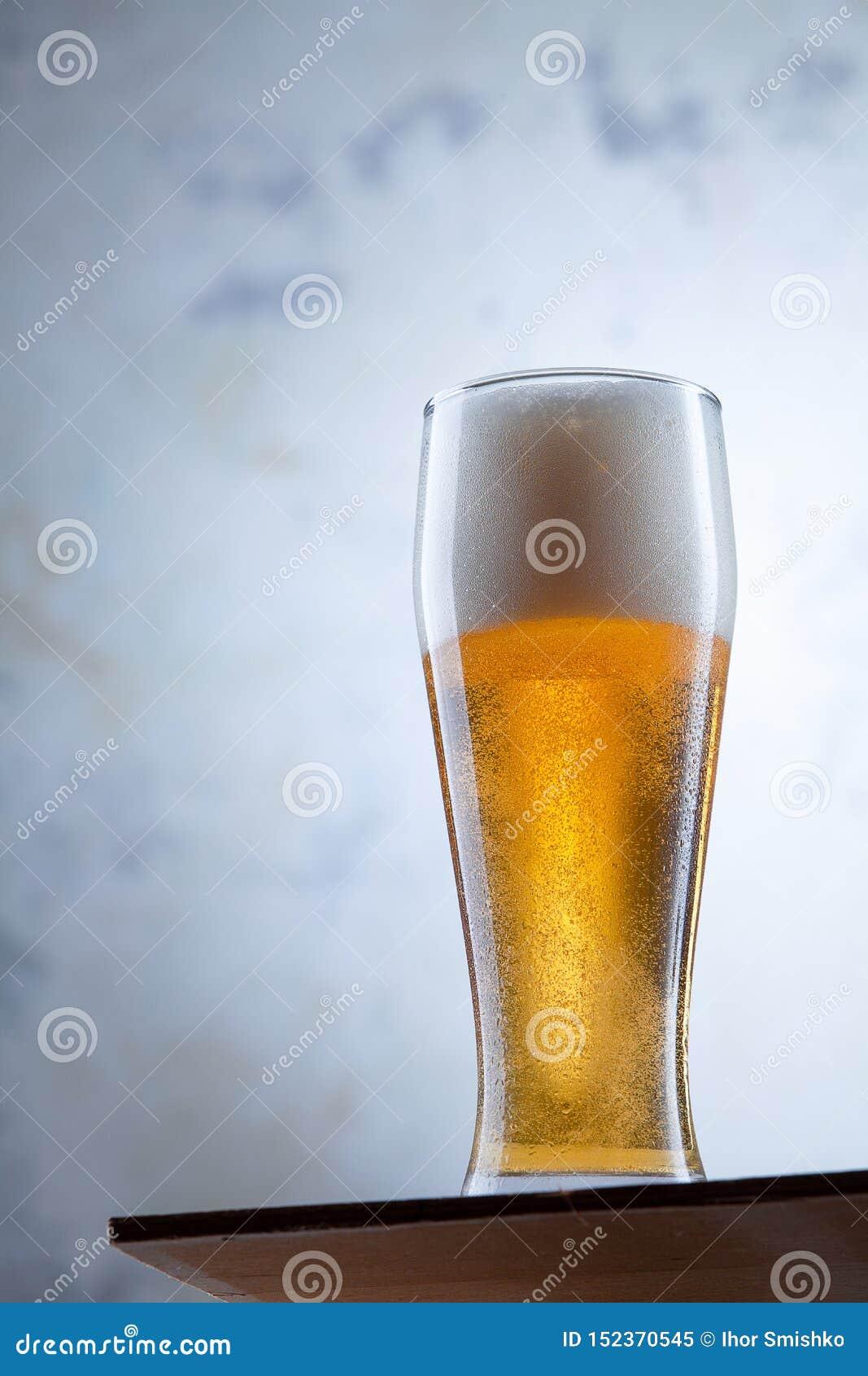 Vista ascendente próxima no vidro frio de suportes da cerveja na frente de um muro de cimento Bebidas frias do álcool Vidro da ce