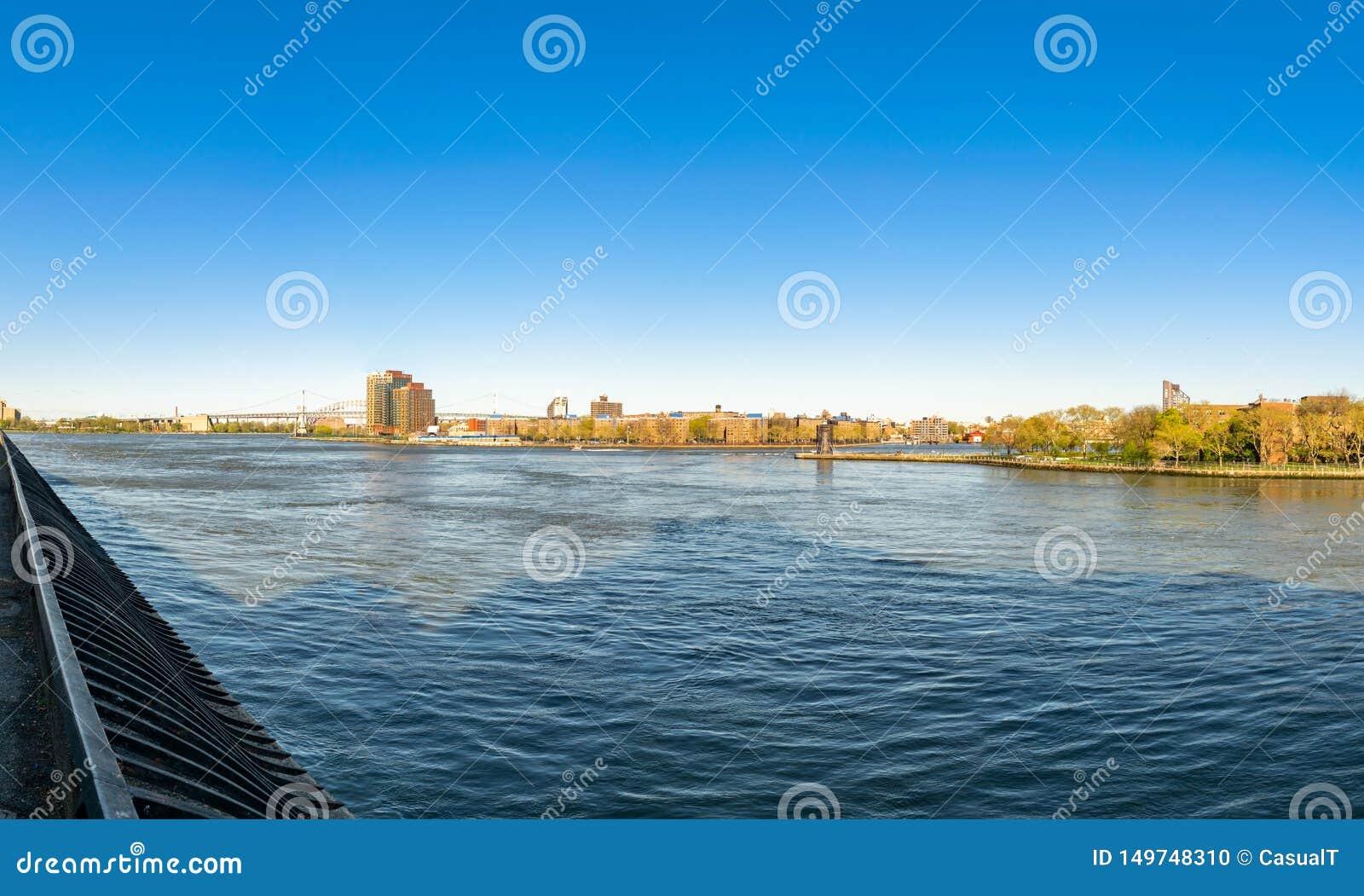 Vista através do East River de New York City, para a ponte de Triborough e as partes de Roosevelt Island e do Queens