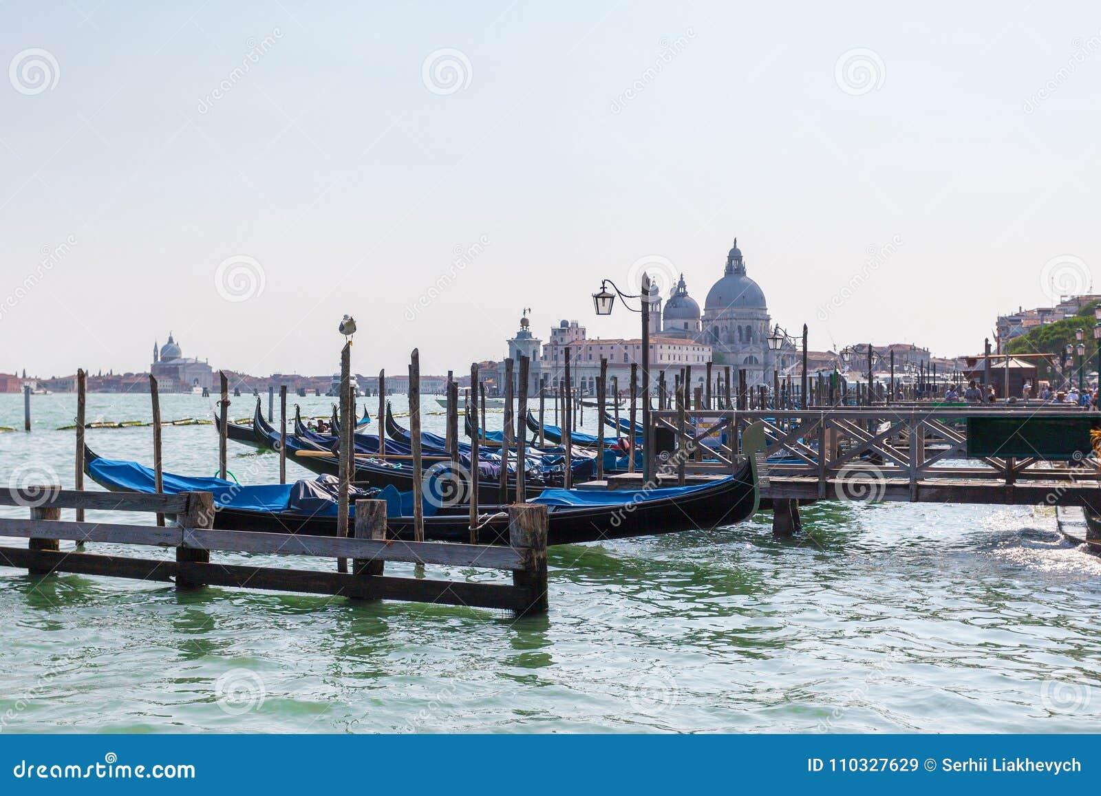 Vista bonita da gôndola tradicional no canal grandioso com di Santa Maria della Salute da basílica em Veneza, Itália