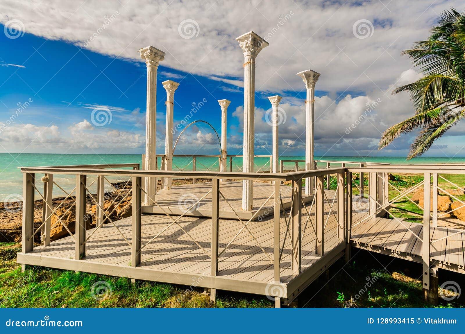 Vista bonita das colunas velhas do miradouro do casamento que estão na plataforma de madeira à moda perto da praia e do oceano tr