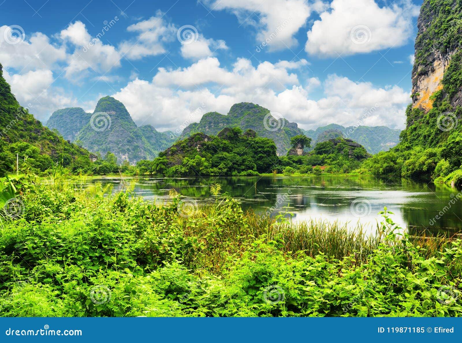 A vista bonita do lago entre o cársico eleva-se em Ninh Binh, Vietname