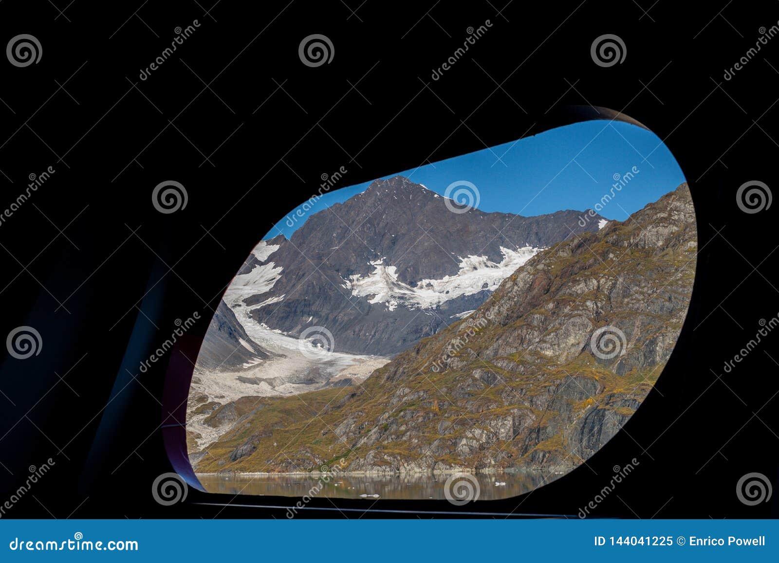 Vista cênico através do furo do porto do navio/janela de montanhas cobertos de neve