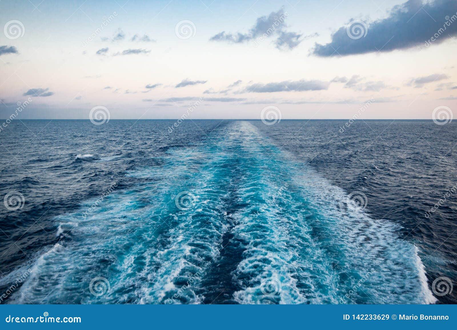 Vista cênico do mar da proa de um navio de cruzeiros luxuoso, contra o nascer do sol em um céu azul bonito