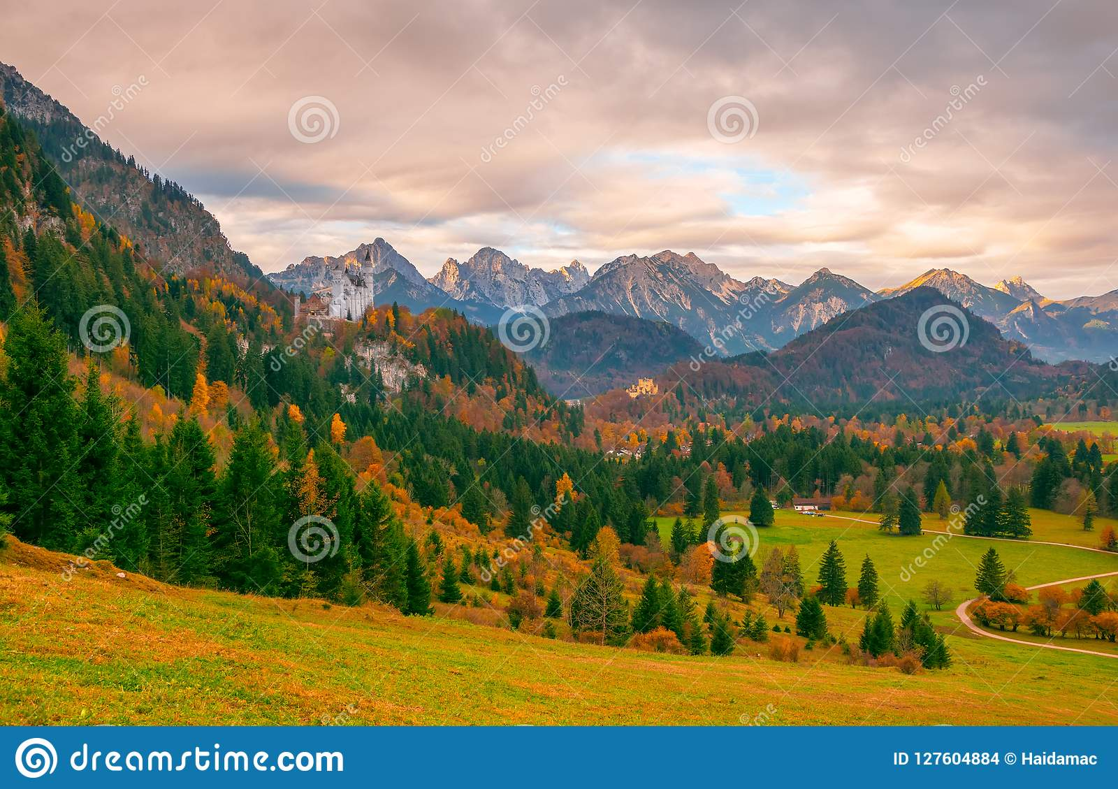 A vista cênico do vale alpino com Neuschwanstein e Hohenschwangau fortifica na manhã do outono