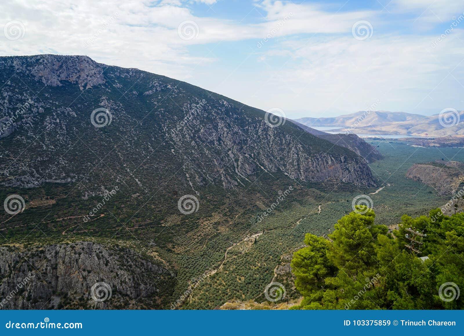 Vista circostante fresca della valle del pendio di montagna di Parnassus, oliveti verdi attraverso il mare ionico con il fondo lu