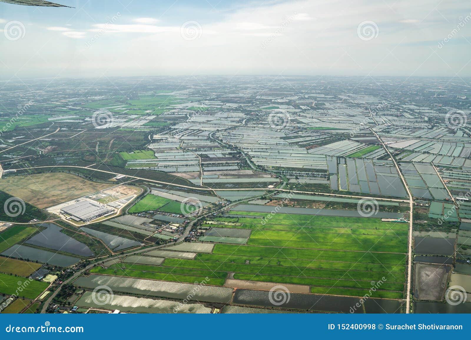 A vista da baixa verde do campo e da exploração agrícola e da cidade no meio de Tailândia Disparou de Jetplane