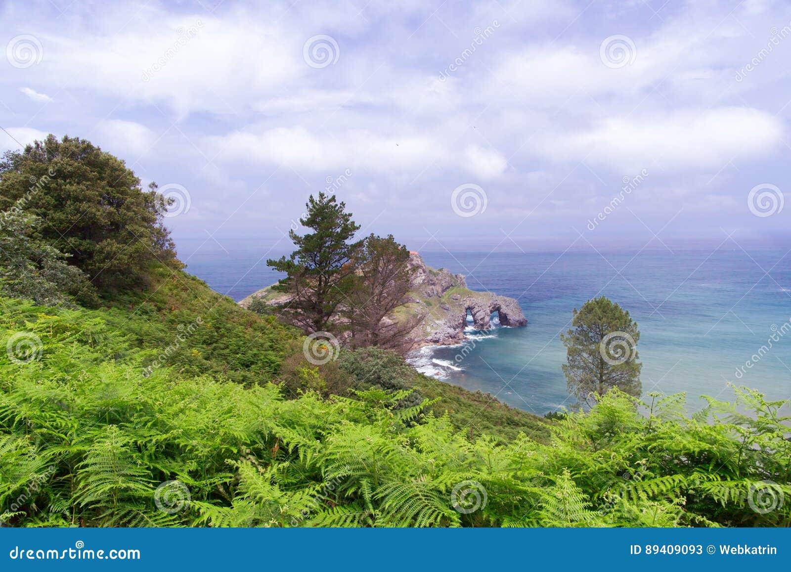 Vista da costa na rocha no oceano com uma capela Donie