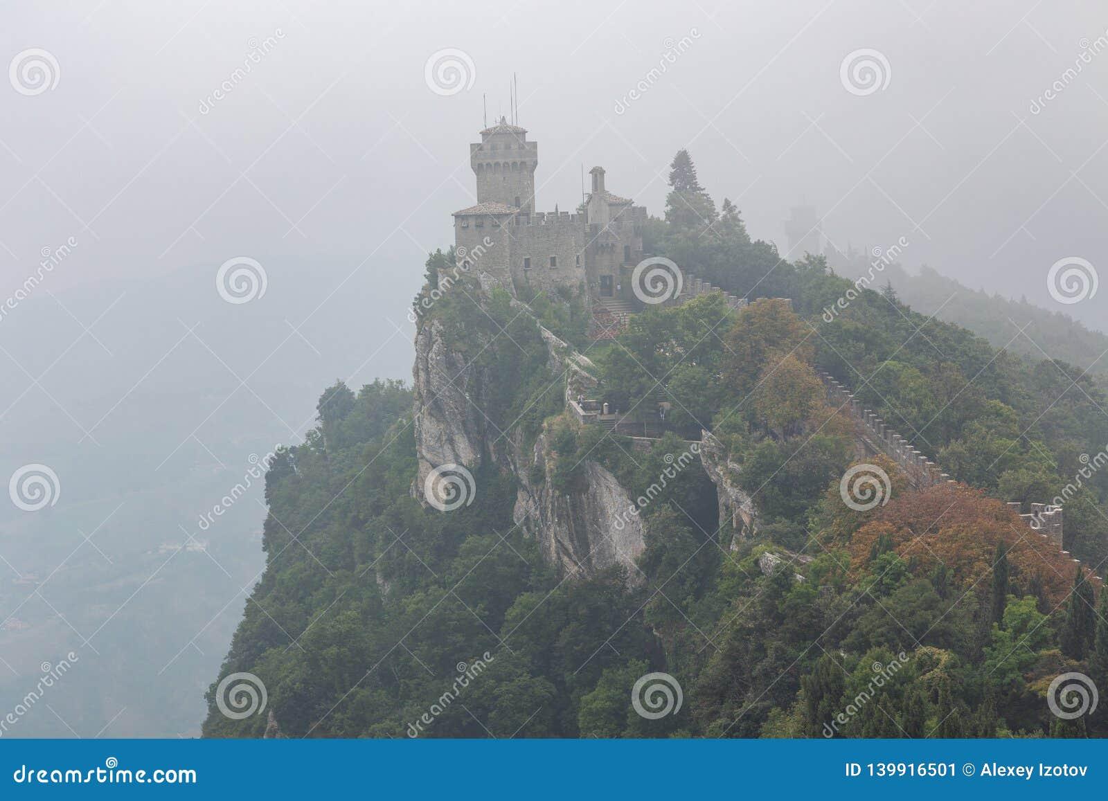 Vista da fortaleza de Guaitta na torre de Falesia segundo em São Marino na névoa