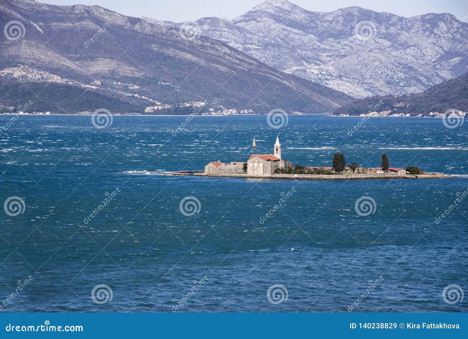 Vista da ilha Gospa od Milo Bay de Otok de Tivat, Montenegro, em um dia de inverno ventoso 2019-02-23 11:49