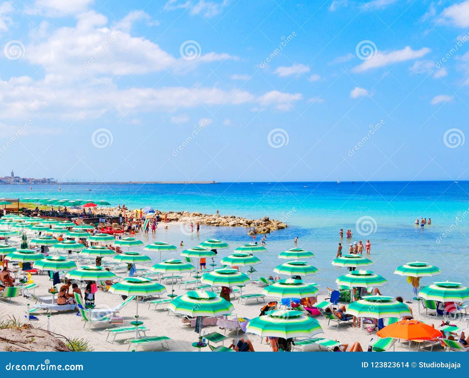 Vista da praia bonita e do mar em Alghero Praia-frequentadores que alugam em vadios do sol