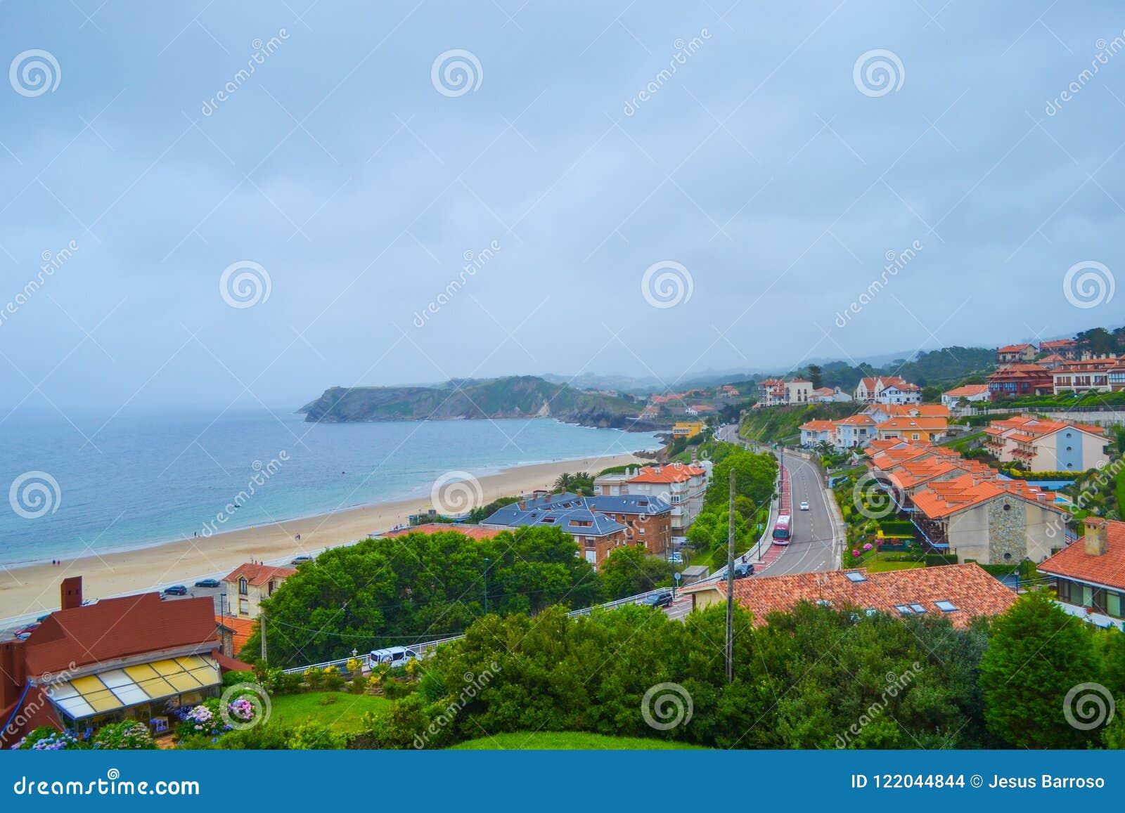 A vista da praia e a cidade de Comillas de Guell e de Martos estacionam n