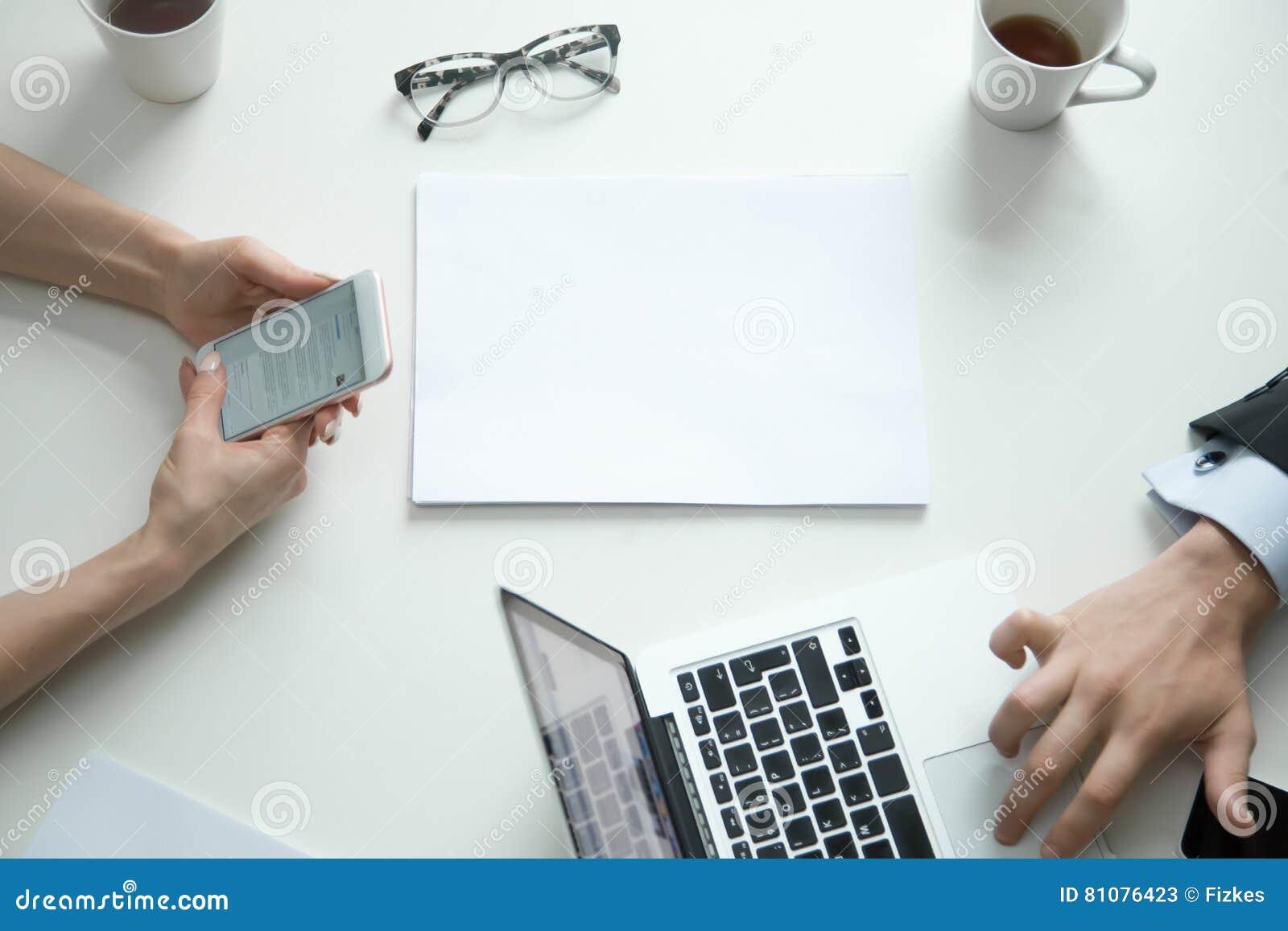 Vista da tavolino dellufficio donna con il telefono uomo sul