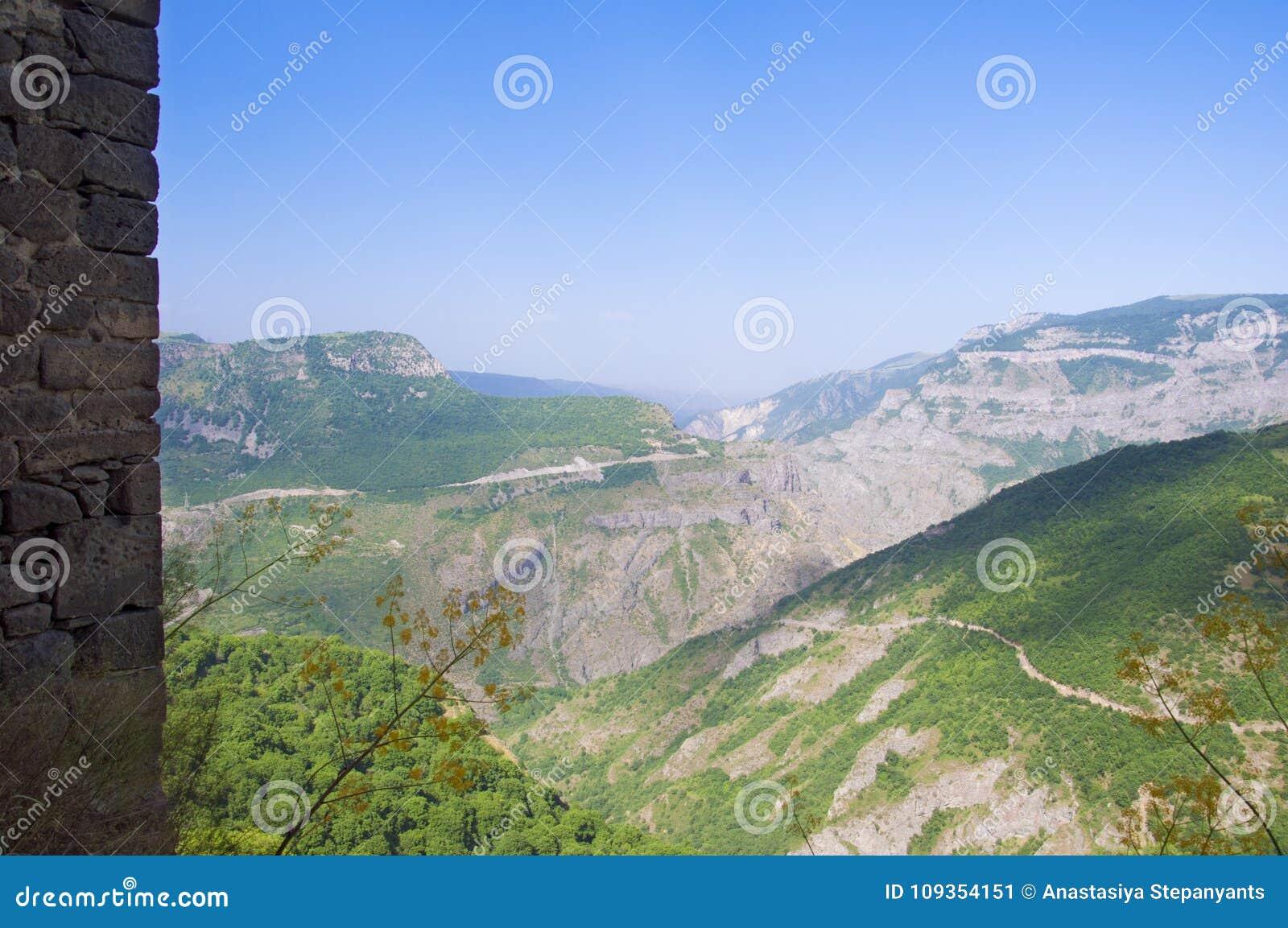 Vista das montanhas verdes céu azul, borda de uma parede de pedra Monastério Tatev, região de Syunik, Armênia