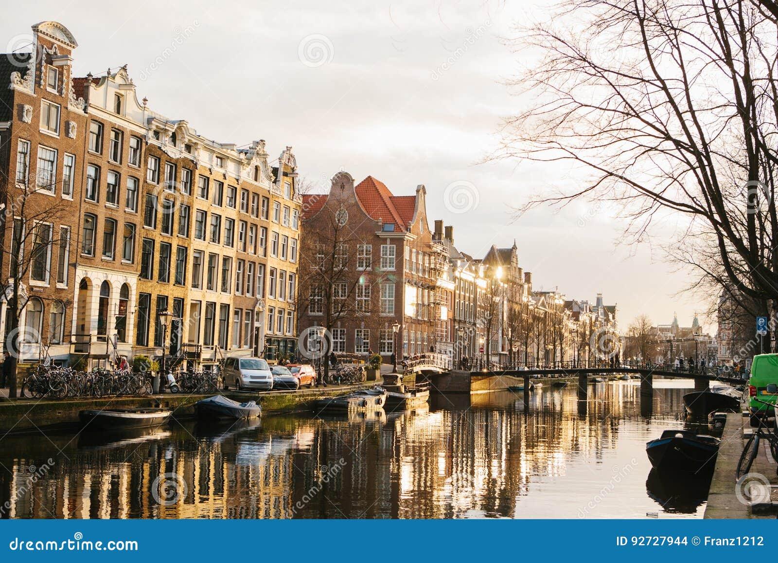 Vista de casas tradicionais em Amsterdão Países Baixos Europa Por do sol noite Casas européias do estilo canaletas