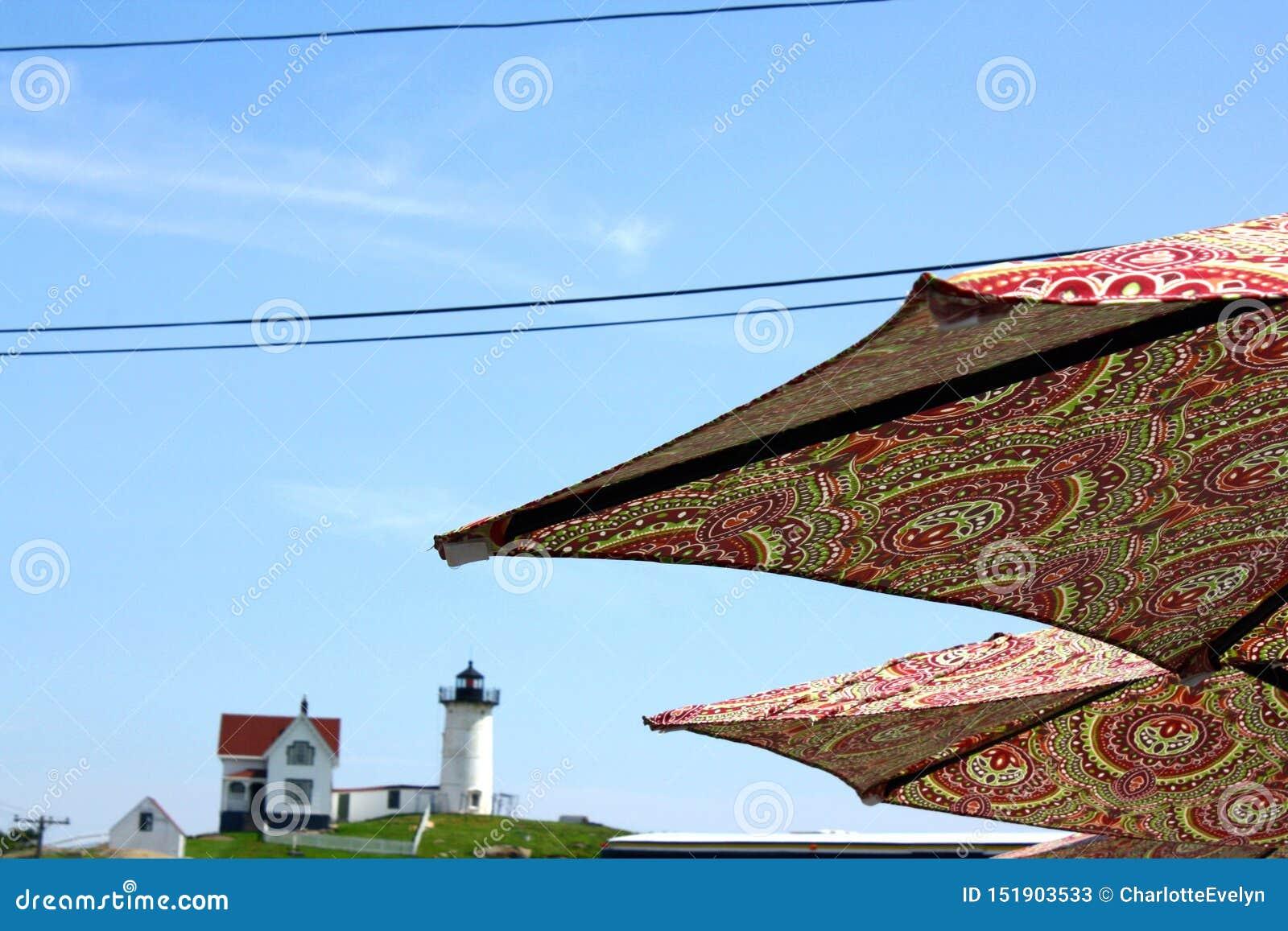 Vista de dos paraguas del estampado con el faro de la protuberancia pequeña en el fondo
