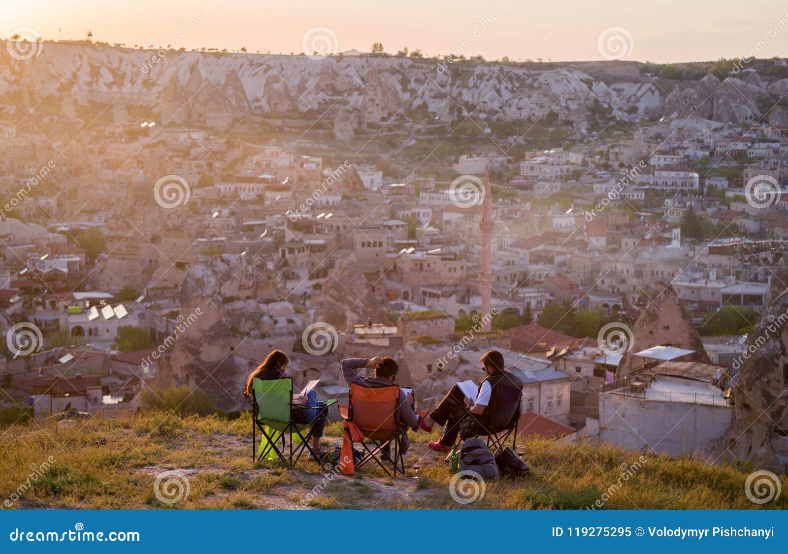 Vista de Goreme en la puesta del sol con la compañía de estudiantes en el primero plano, visión desde la parte posterior Cappadoc