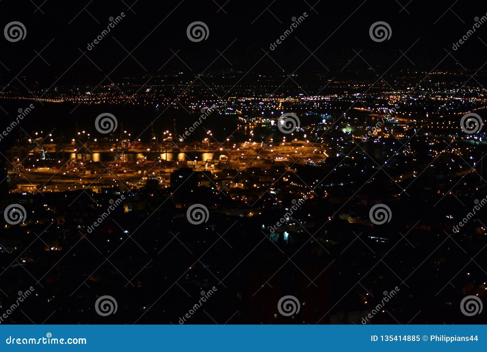 Vista de Haifa e do porto do centro dos jardins de Bahai em Mt Carmel na noite, Israel