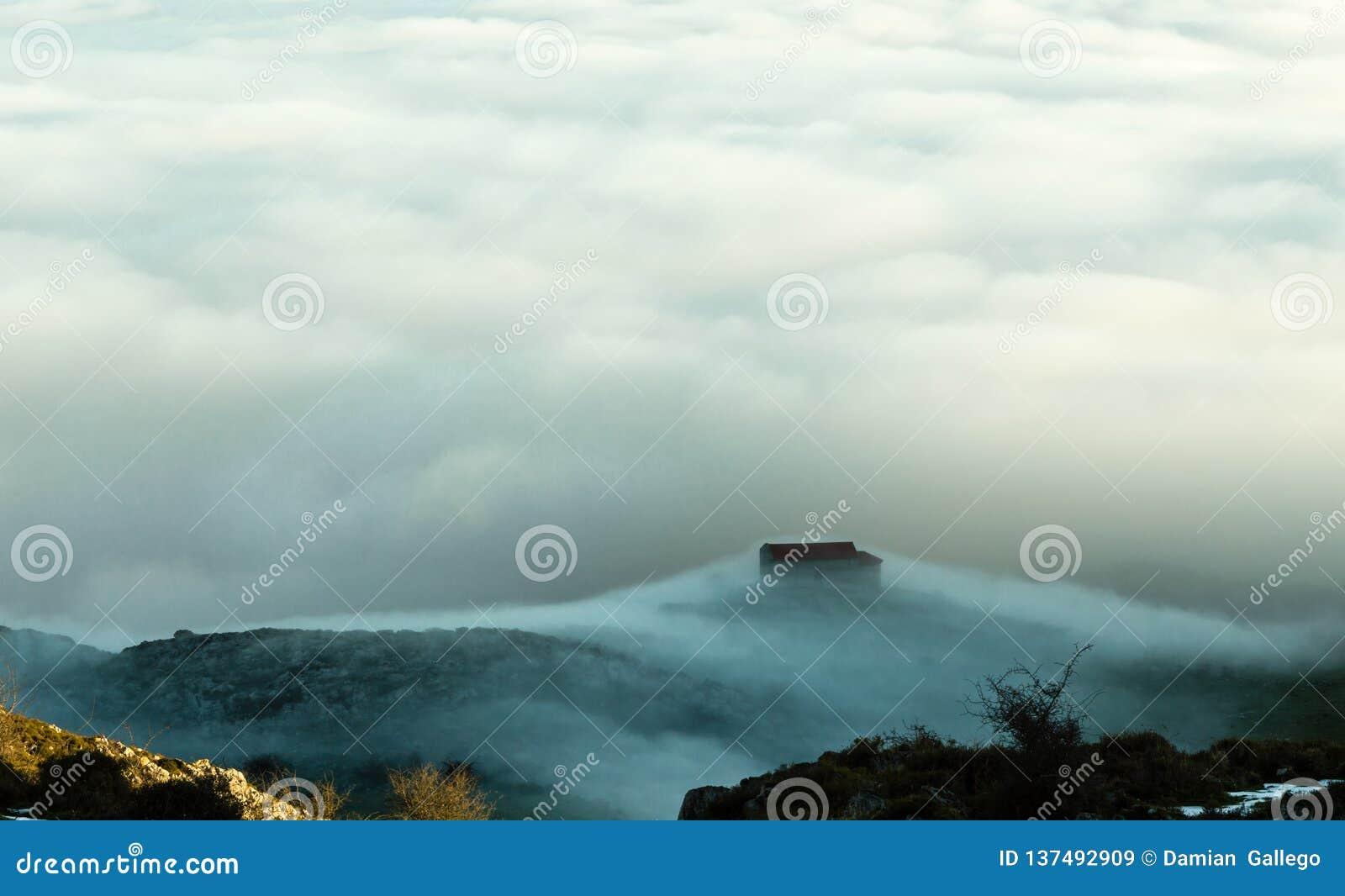 Vista de la ermita del La Magdalena, en el soporte Monsacro de la montaña, en el amanecer Con las nubes de un mar del fondo Astur