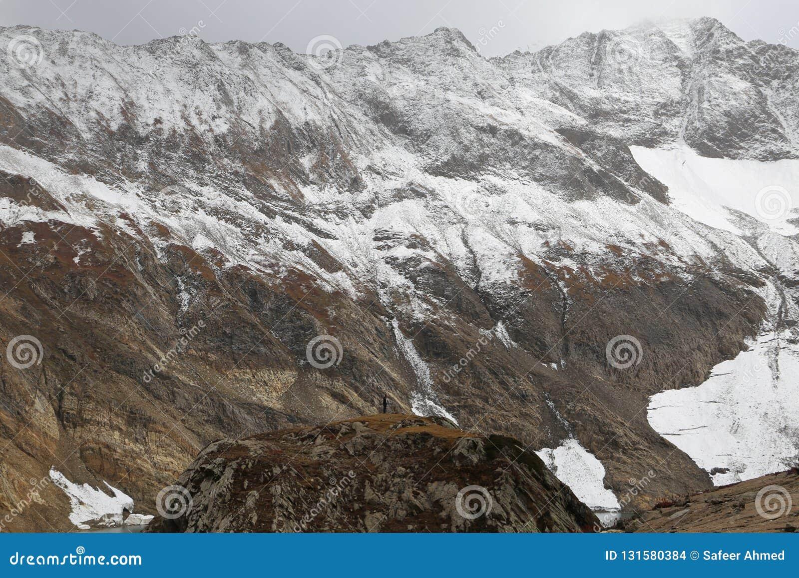 Vista de la montaña montañosa nevosa debajo de las nubes oscuras