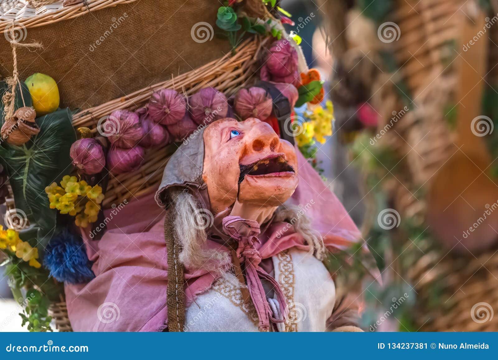 Vista de la muñeca del granjero, manipulada con la gente dentro, llevando la cesta tradicional grande, en el mercado medieval de