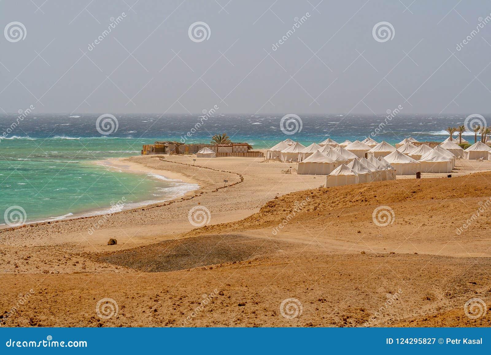 Vista de las ondas salvajes que se estrellan sobre Coral Reef y las tiendas del beduino en viento en la playa en Marsa Alam