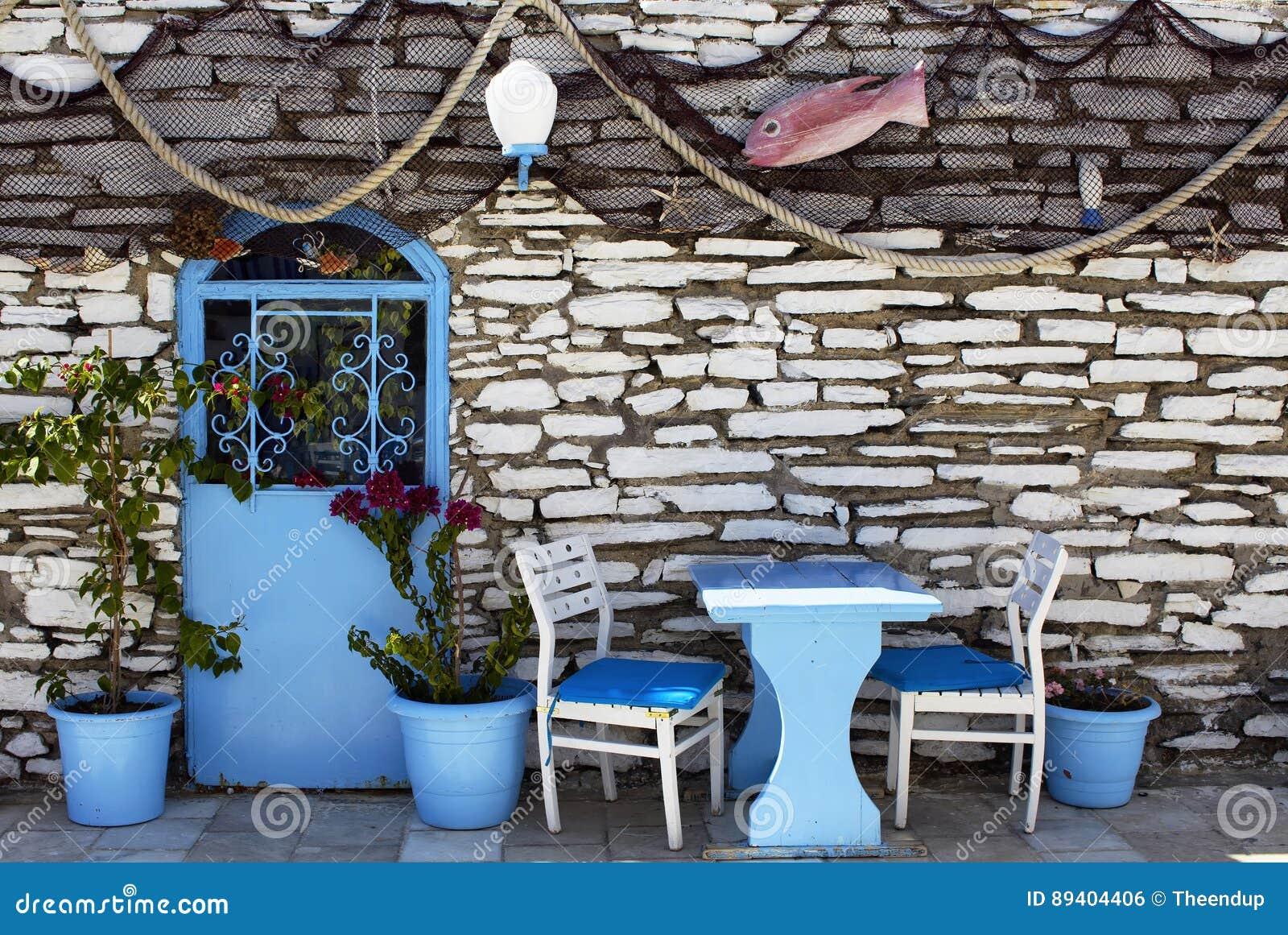 Vista de redes dos peixes, de cadeiras azuis, de porta, de potenciômetros e da parede de pedra
