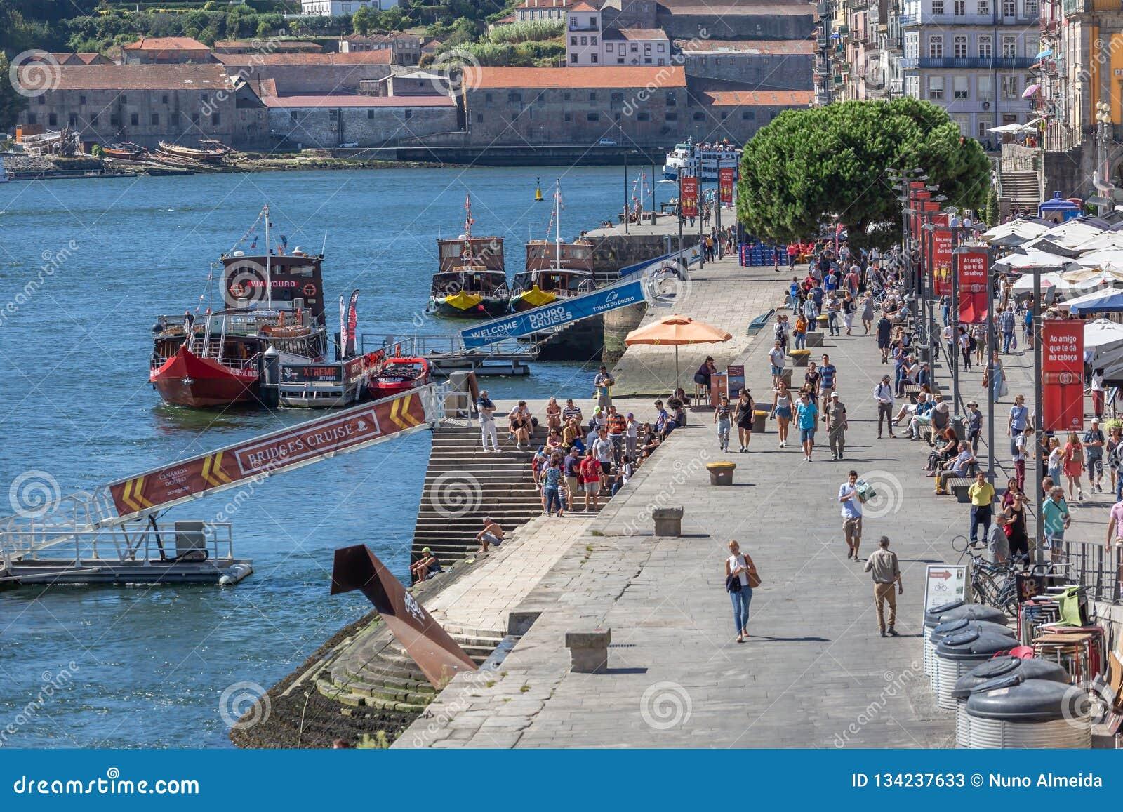 Vista dei bacini di Ribeira sulla città di Oporto, con la gente turistica, le barche ricreative, il fiume del Duero e le costruzi