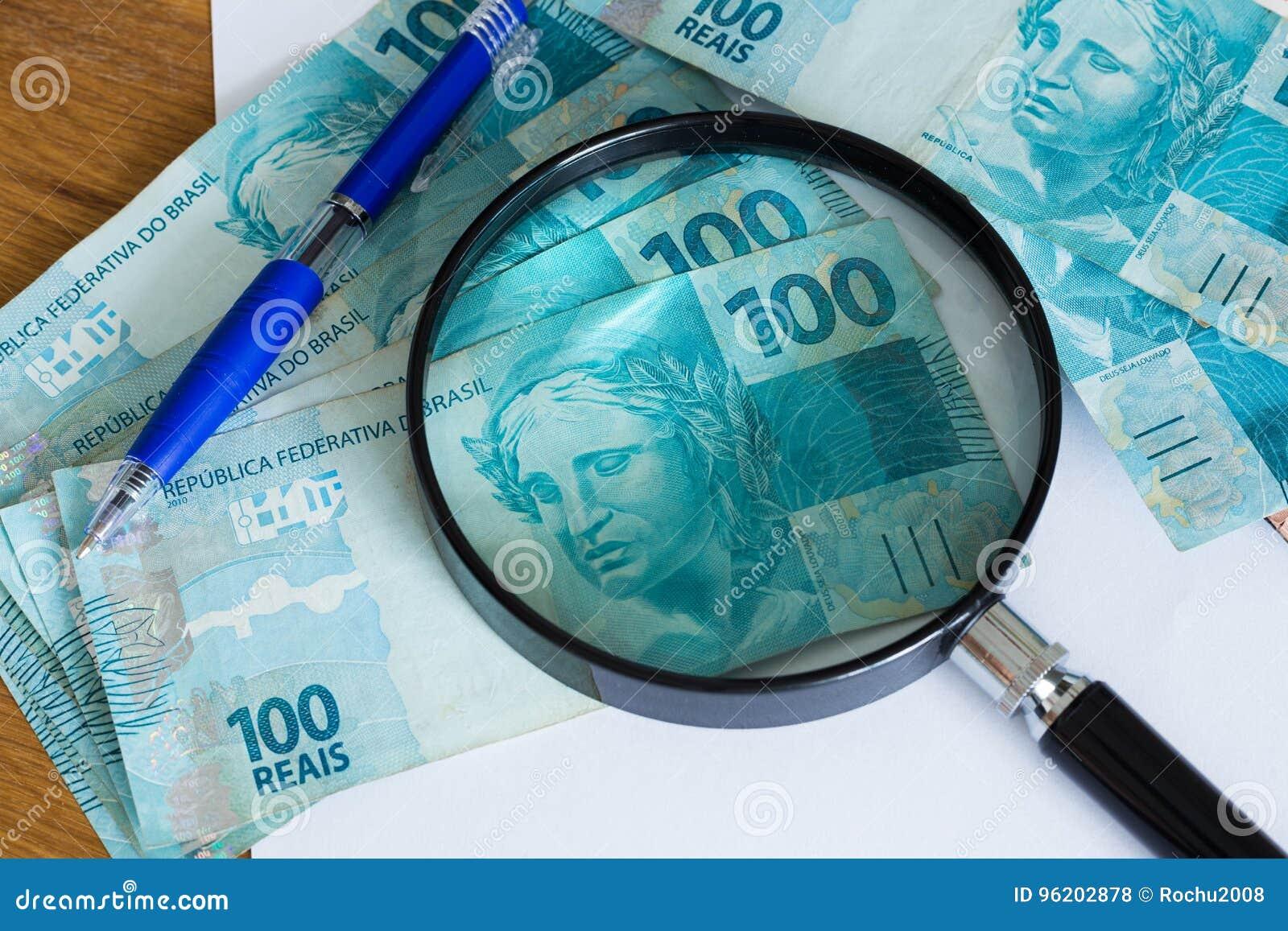 Vista del dinero brasileño, de los reais, del arriba nominales con una hoja de papel y una pluma para los cálculos