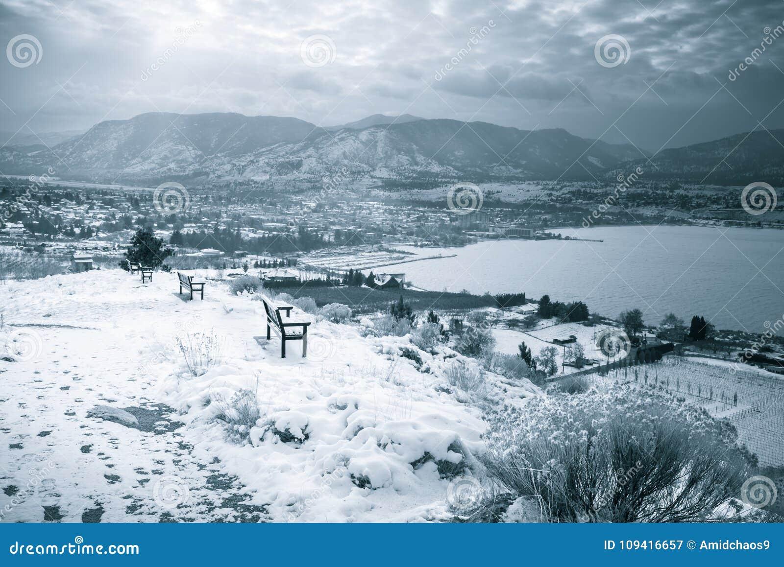 Vista del paesaggio di inverno della città, del lago e delle montagne innevate