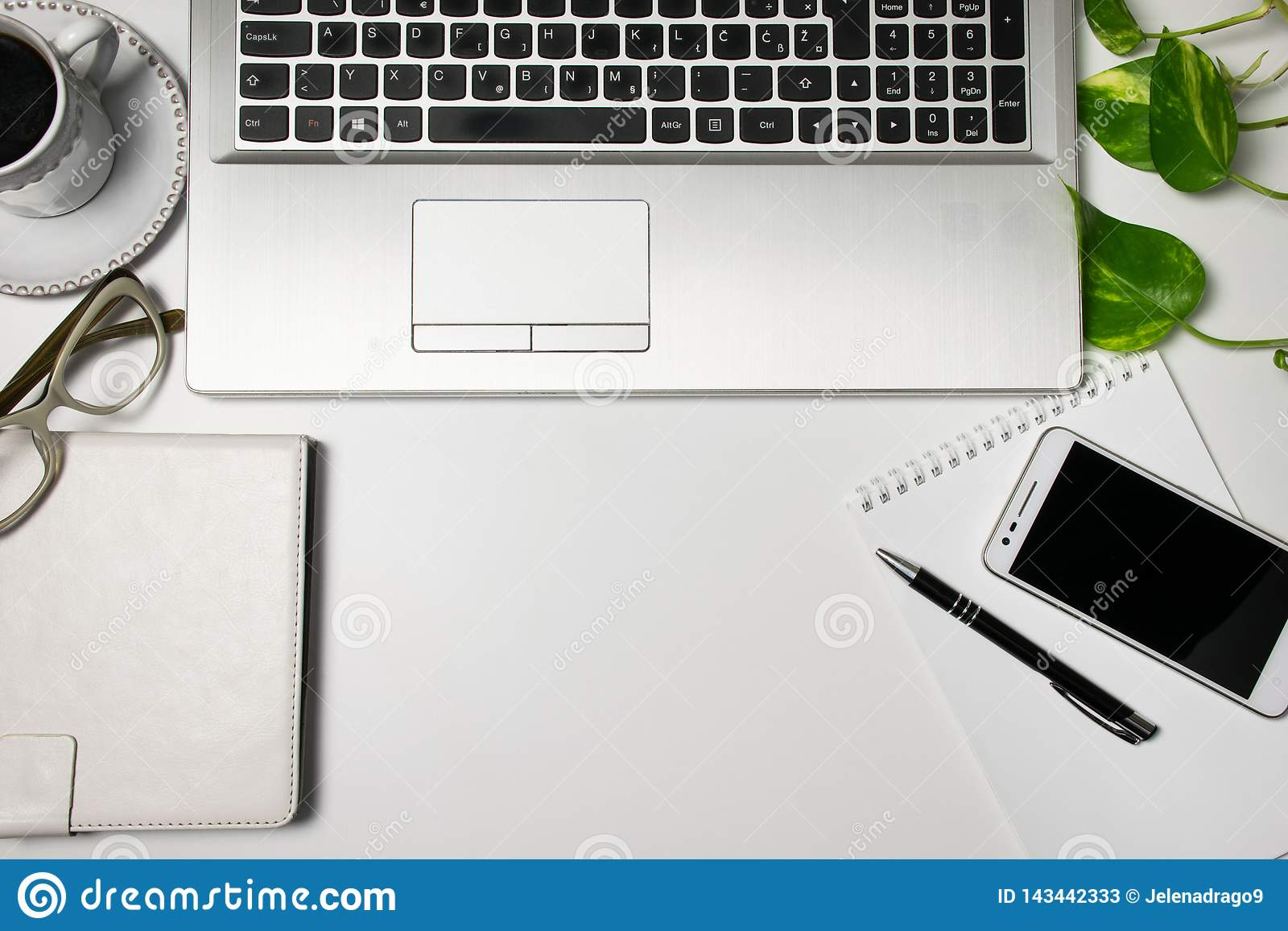 Vista del piano d appoggio della scrivania e rifornimenti, computer portatile, tazza di caffè nero, vetri, pianta, cellulare su f