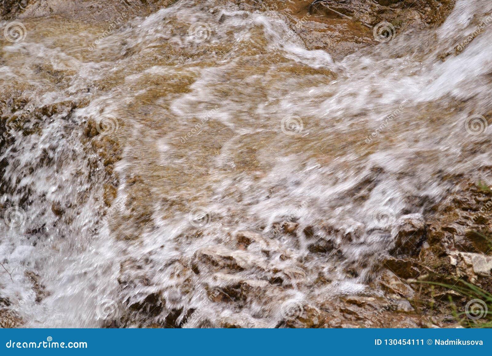 Vista del primo piano ad acqua pura che entra sulle rocce nelle montagne
