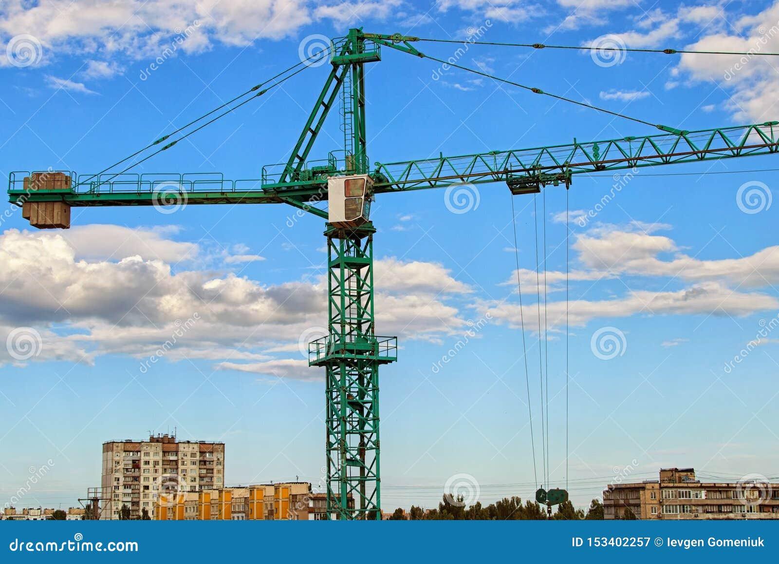 Vista del primo piano della gru contro cielo blu con le belle nuvole bianche Gru a torre verde che costruisce il nuovo edificio r