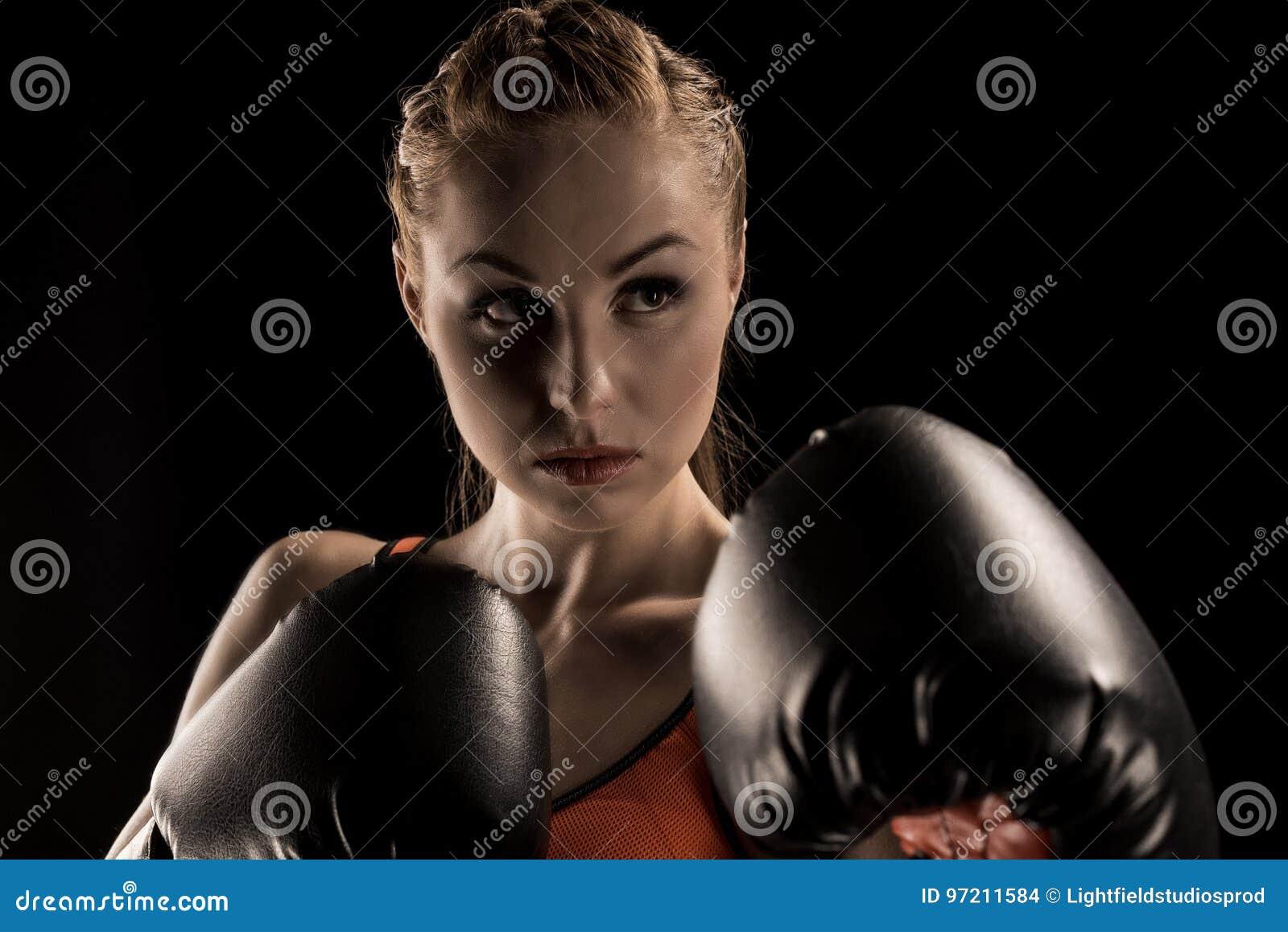 Vista del primo piano di giovane pugilato aggressivo della sportiva in guantoni da pugile