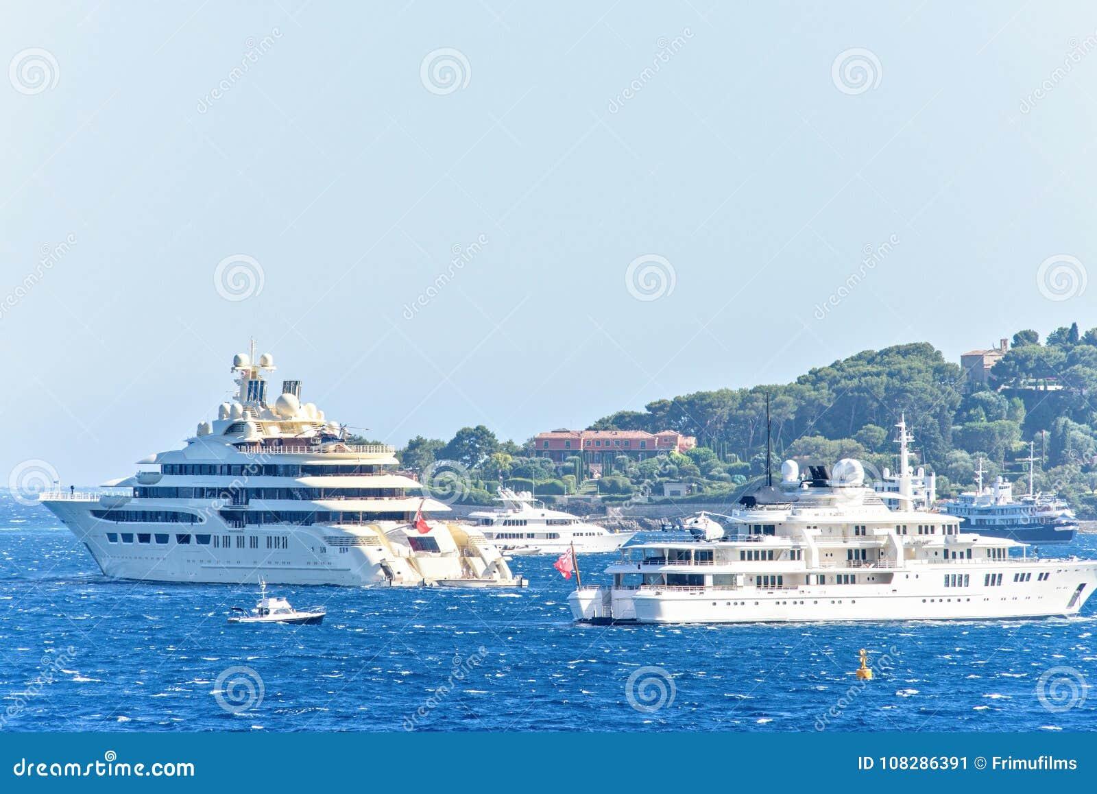 Vista del primo piano di luce del giorno agli yacht bianchi con gli elicotteri a bordo