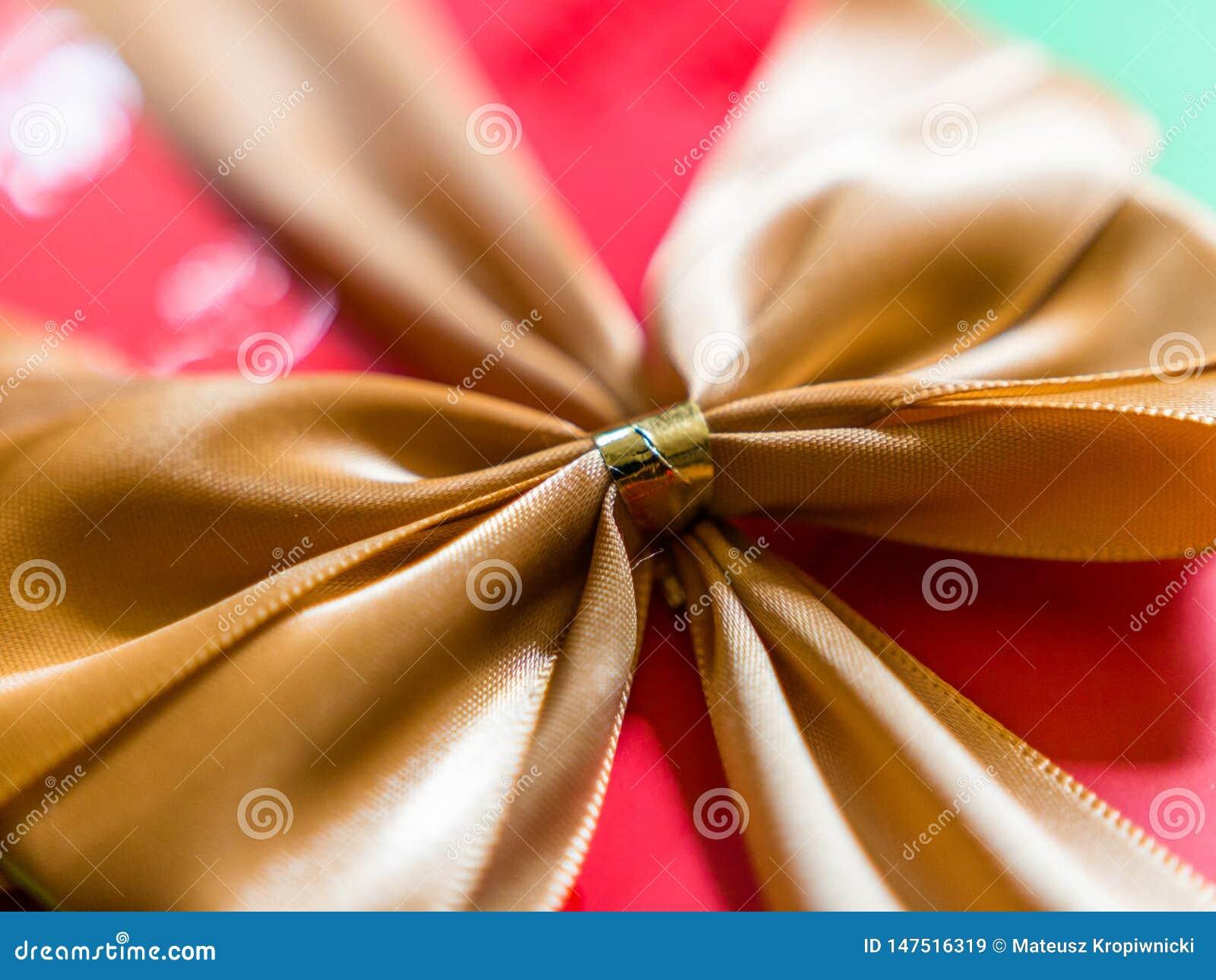 Vista del primo piano del nastro o dell arco dell oro sul contenitore di regalo rosso